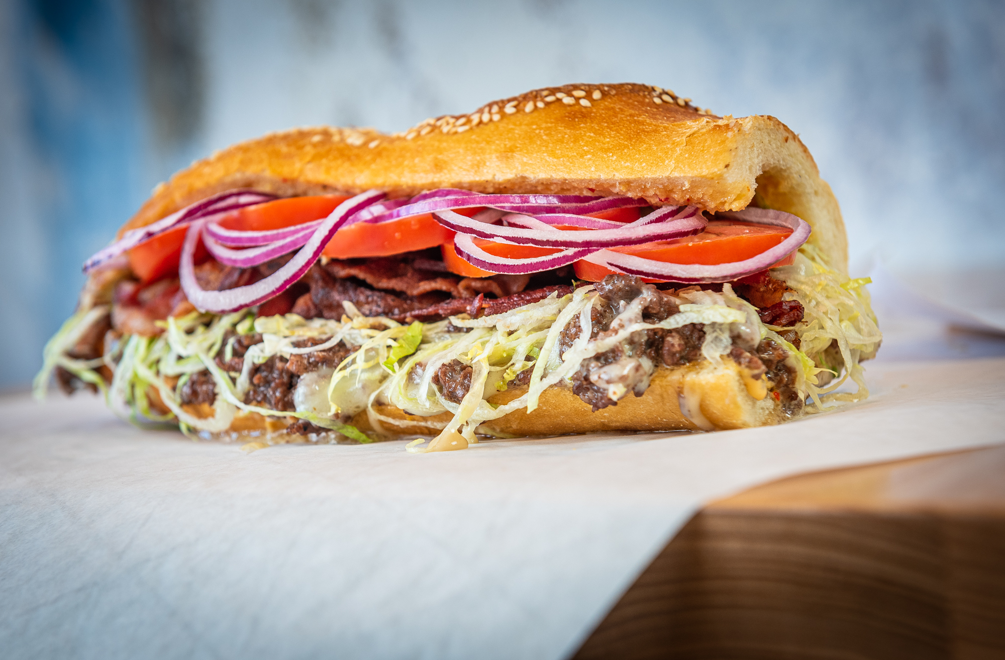 A Philly Special cheesesteak from Grazie Grazie shows off layers of grass-fed beef, Cooper sharp provolone, lettuce, red onion, and tomato on a golden roll