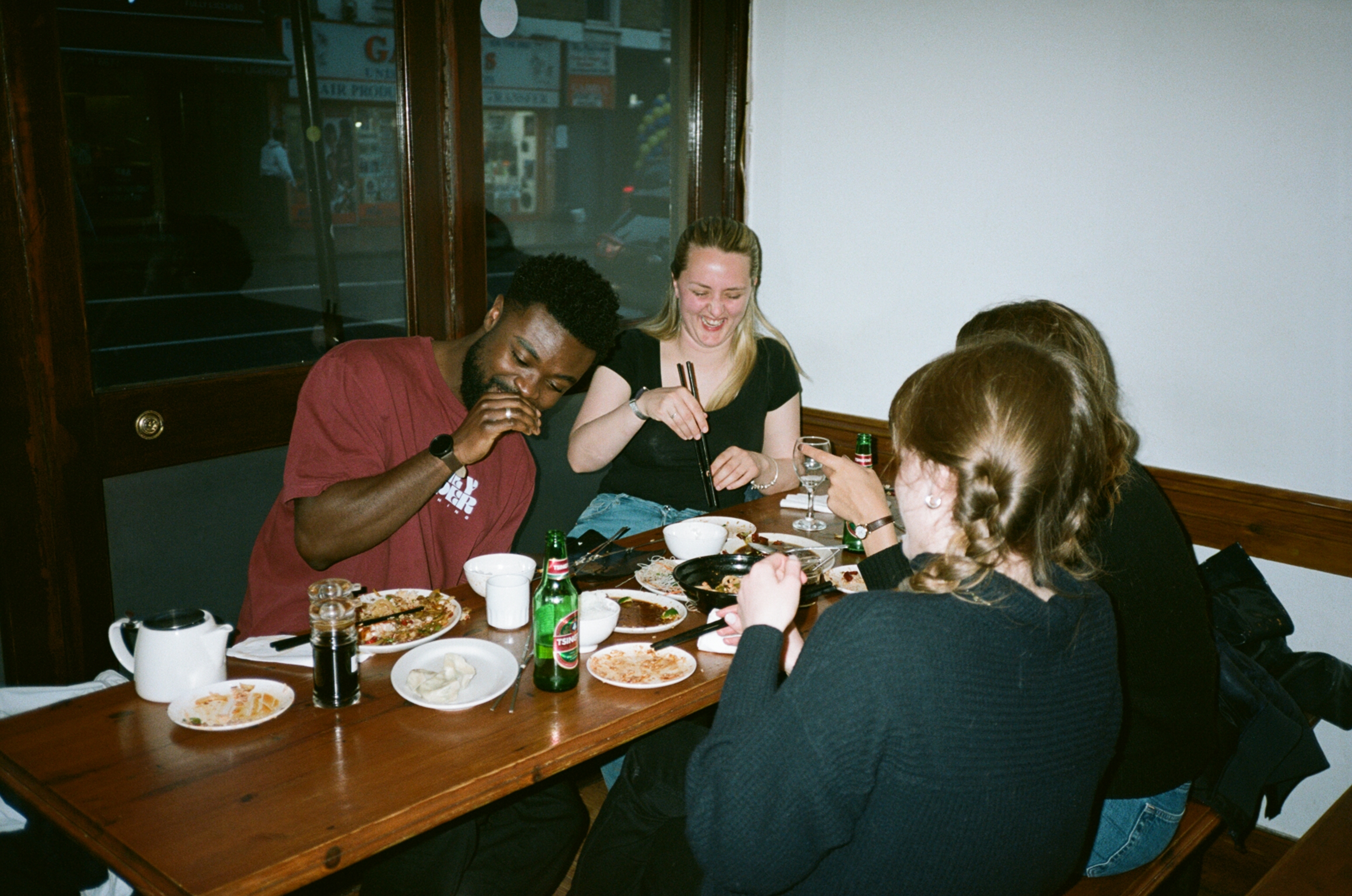Four customers tuck into a meal at at table inside Silk Road in Camberwell