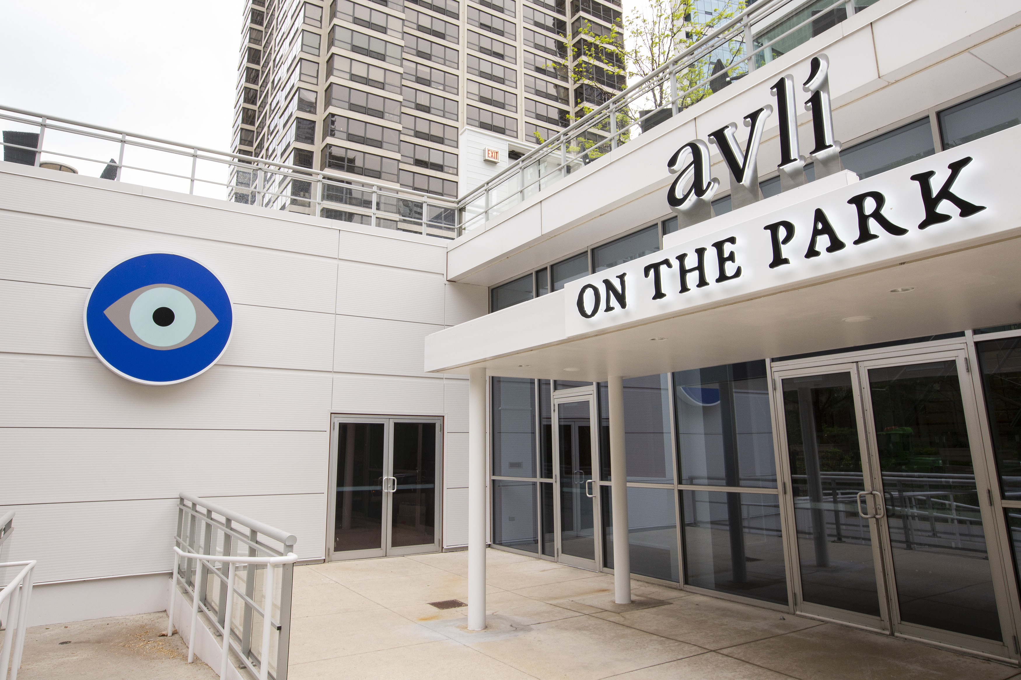"""A white restaurant entrance with a sign that reads """"Avli on the Park"""" and a large blue eye symbol."""