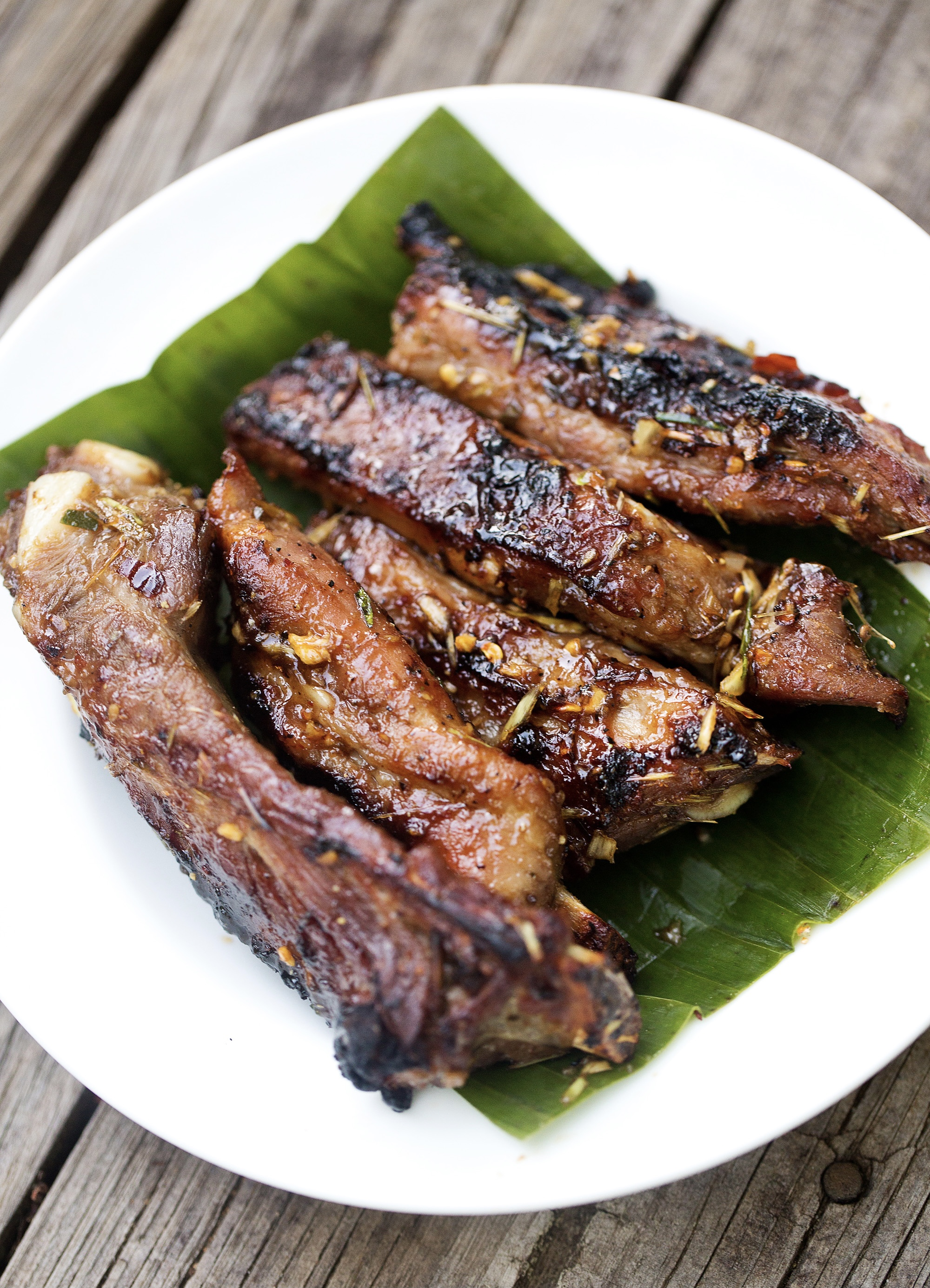 Five glistening barbecue lemongrass ribs sit atop a banana leaf on a white plat