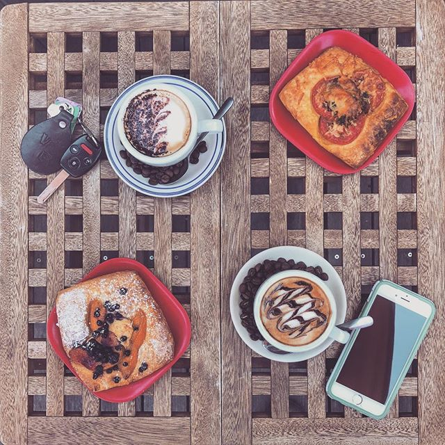 French toast, two lattes, and a sandwich sit on a table, adjacent an iPhone and a set of car keys