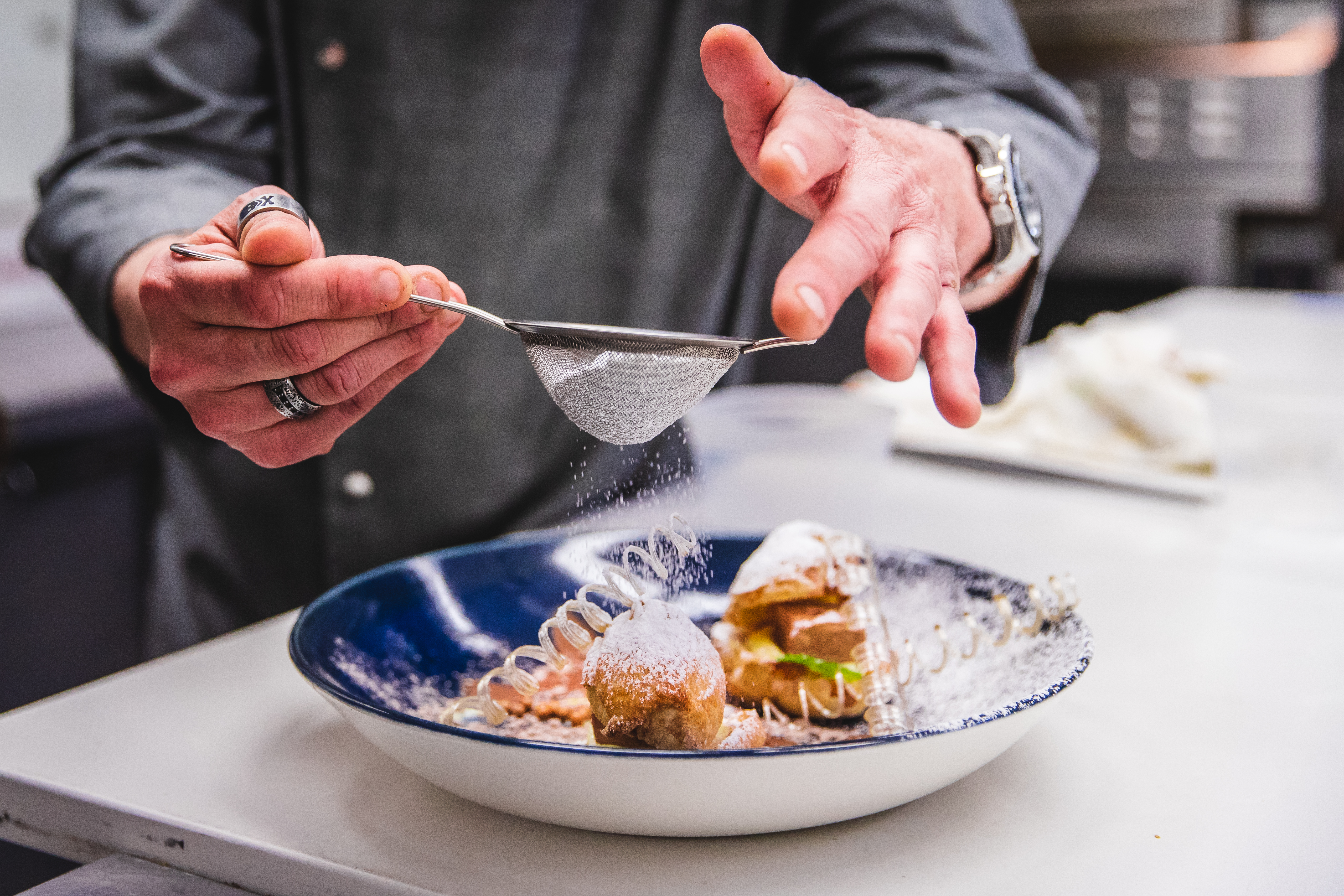 A pair of hands dust a pastry dessert with powdered sugar through a small sieve