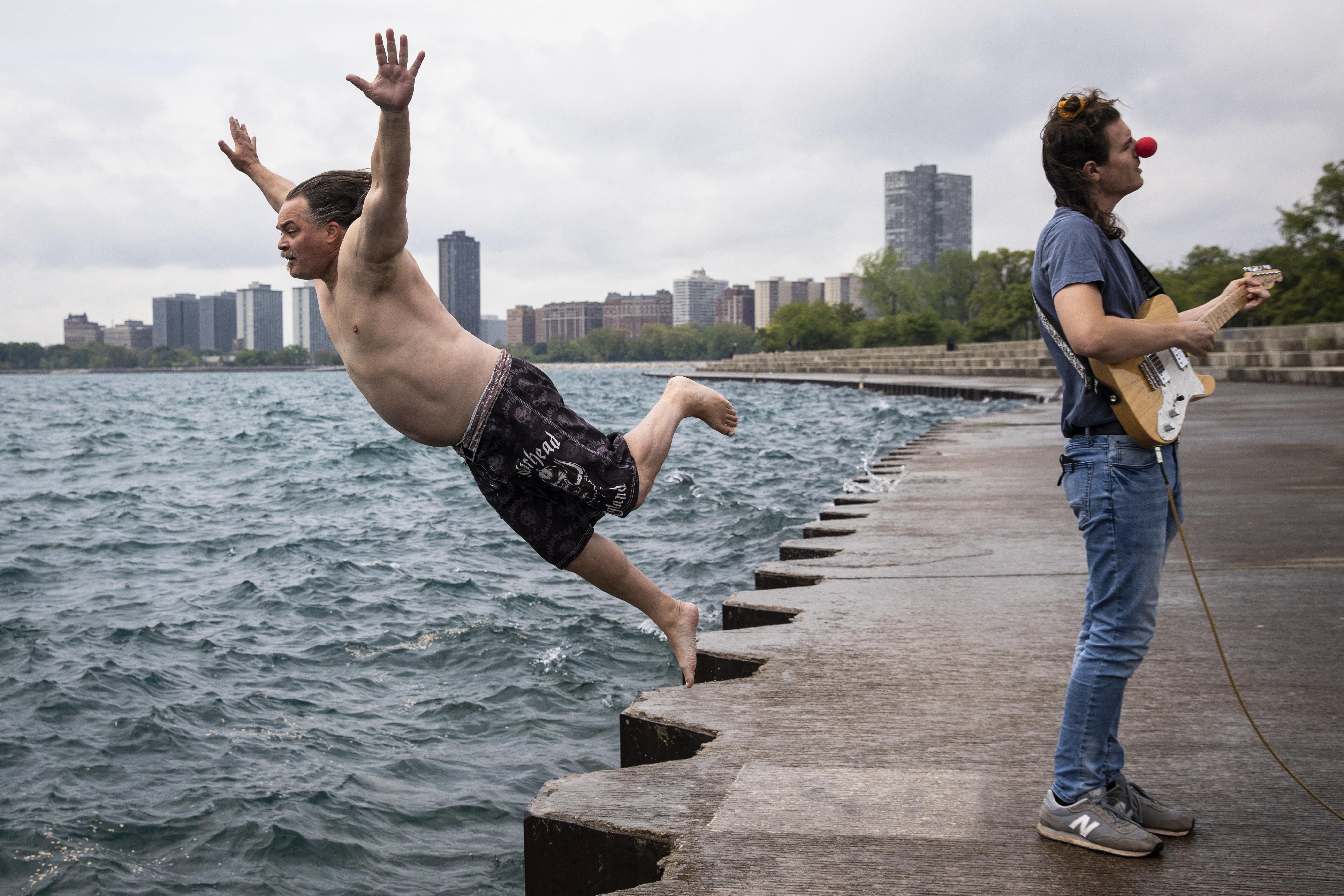 "Dan O'Conor, who calls himself the Great Lake Jumper, dives into Lake Michigan near Montrose Harbor while guitarist Cam Mahai sings ""EndTimes."""