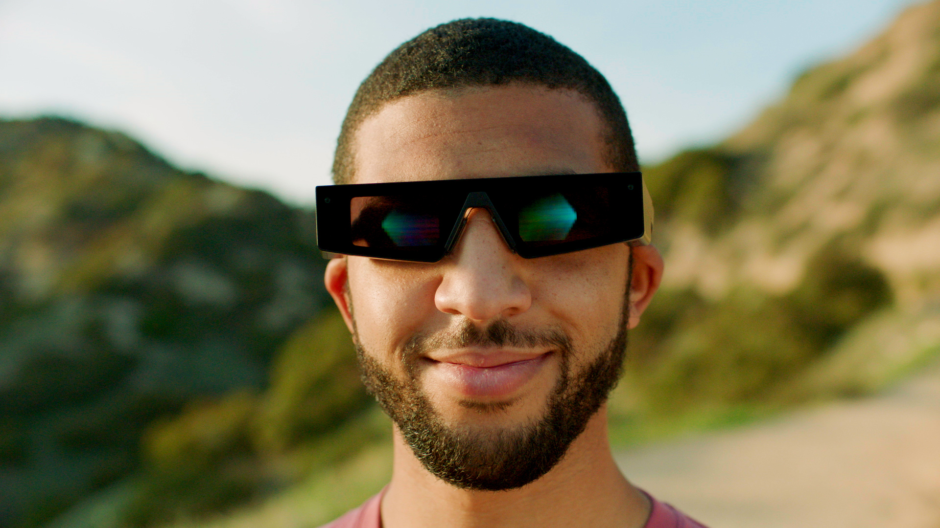 A man wearing Snap's fourth-gen Spectacles, which are black with angular frames.