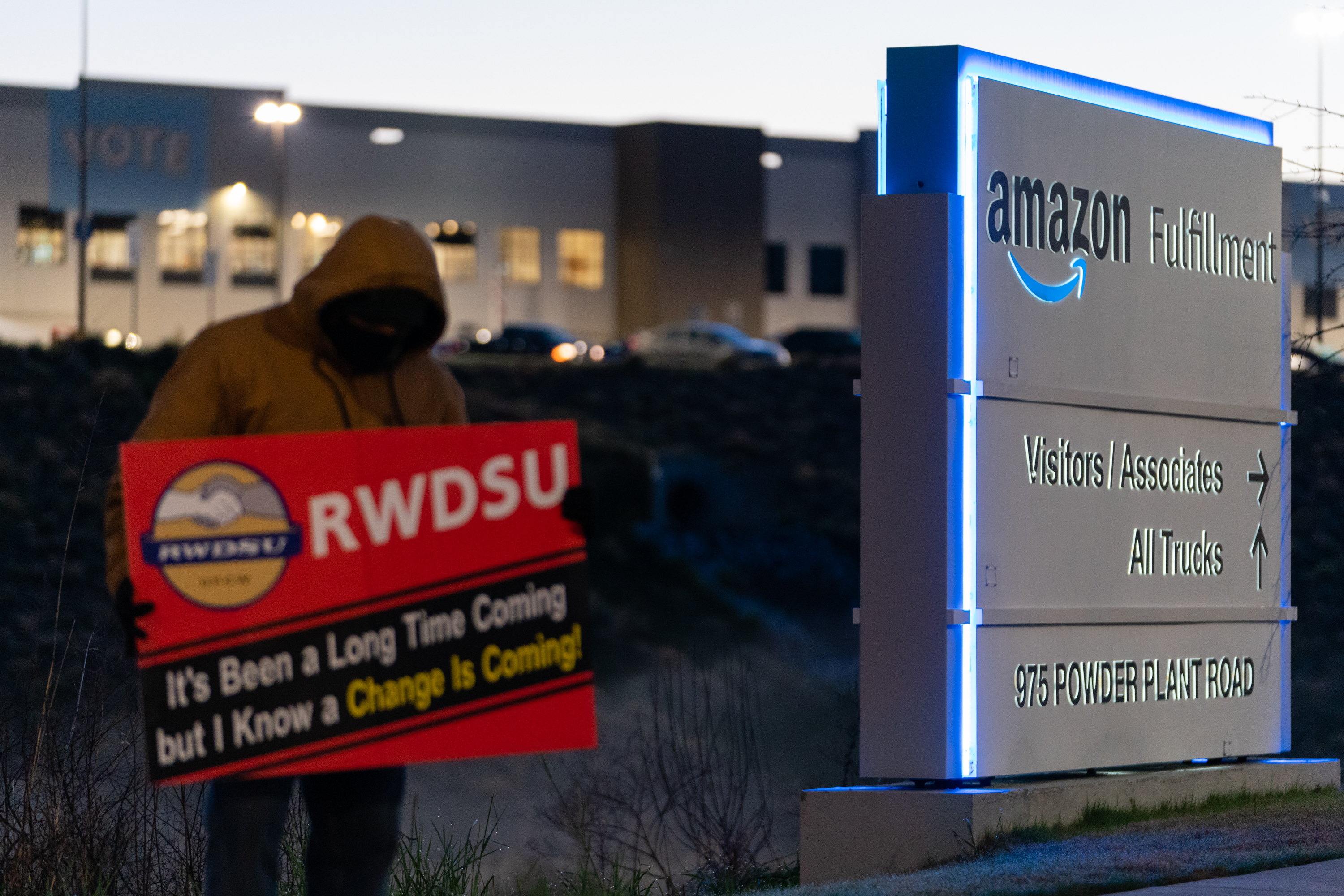 """An RWDSU representative holds a sign that reads """"RWDSU: It's been a long time coming but I know a change is coming"""" outside the Amazon fulfillment warehouse at the center of a unionization drive on March 29, 2021, in Bessemer, Alabama."""
