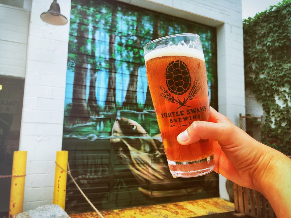 A hand holds a full glass of beer up against a mural of a turtle in a swamp