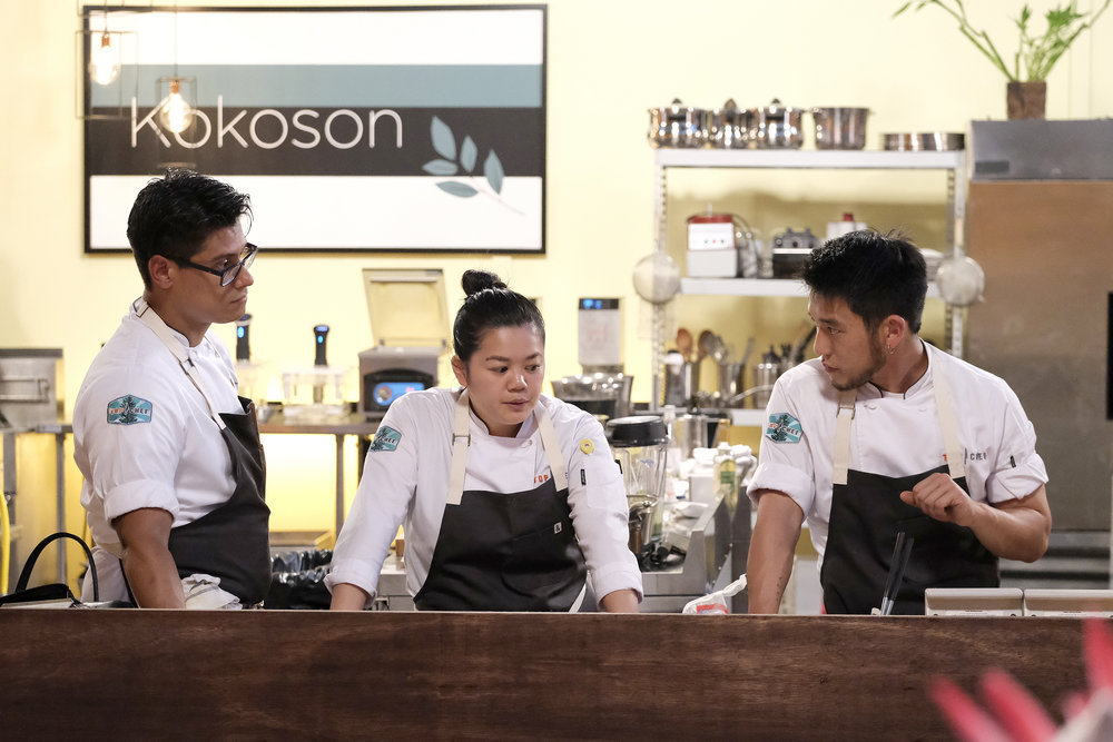 Three chefs stand at a counter