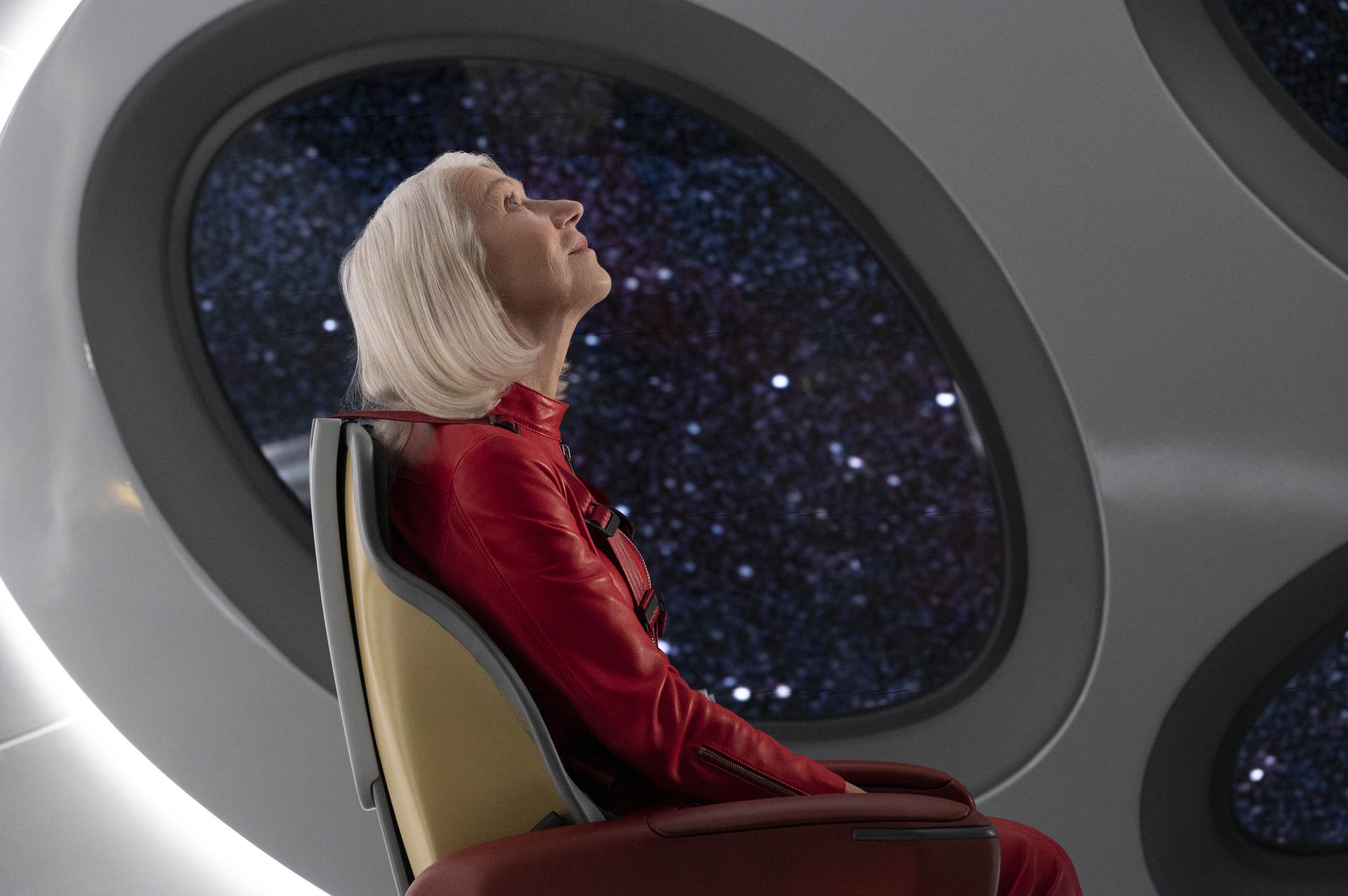 Helen Mirren, in a red coverall, sits in a futuristic silver chair in front of a portal looking out into space in Solos