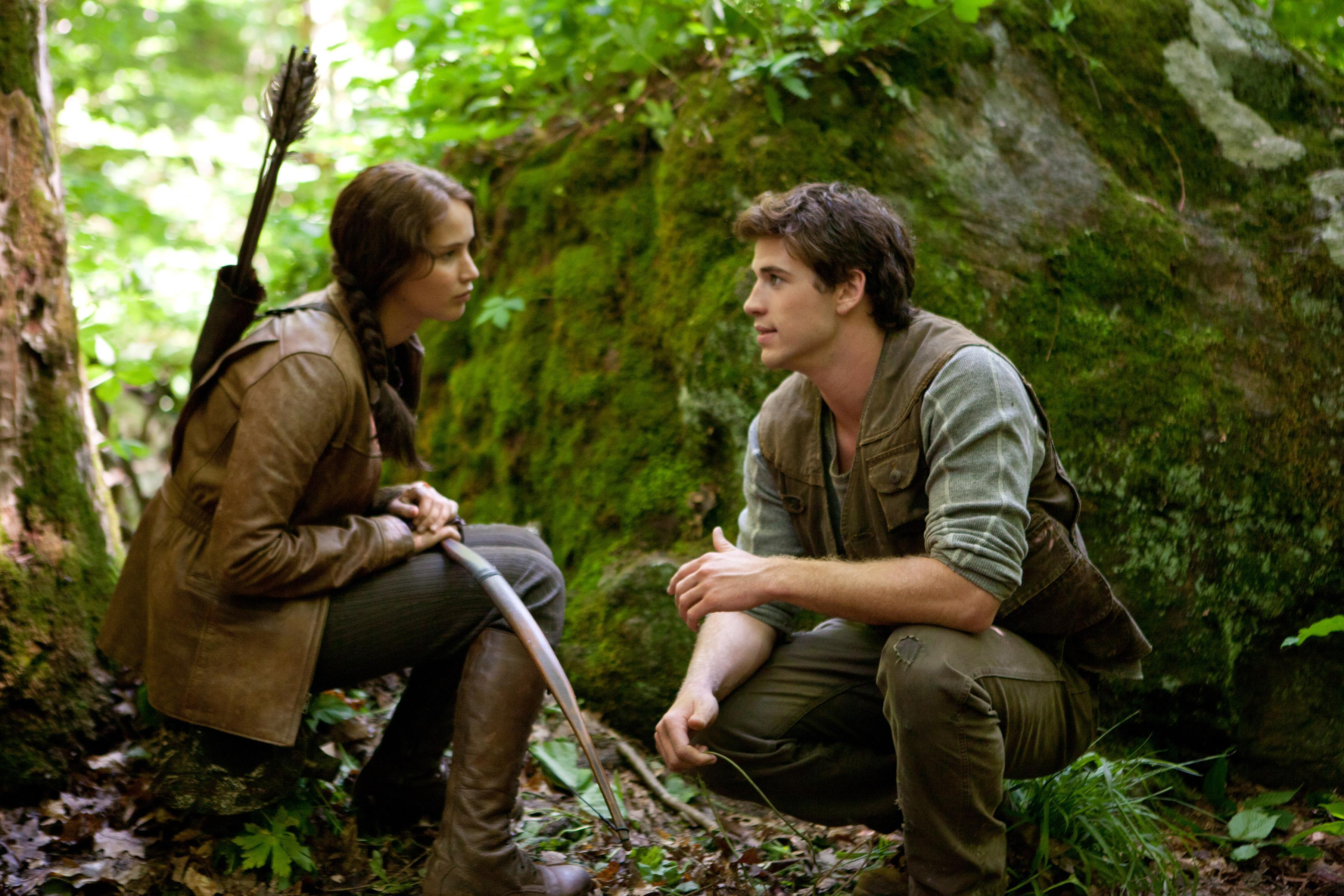Jennifer Lawrence as Katniss Everdeen and Liam Hemsworth as Gale Hawthorne pause together in the forest in The Hunger Games