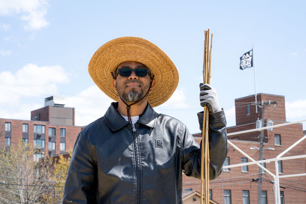 """Man wearing hat holds up bamboo poles; in the background, a """"Black Lives Matter"""" flag flies from a building behind him."""