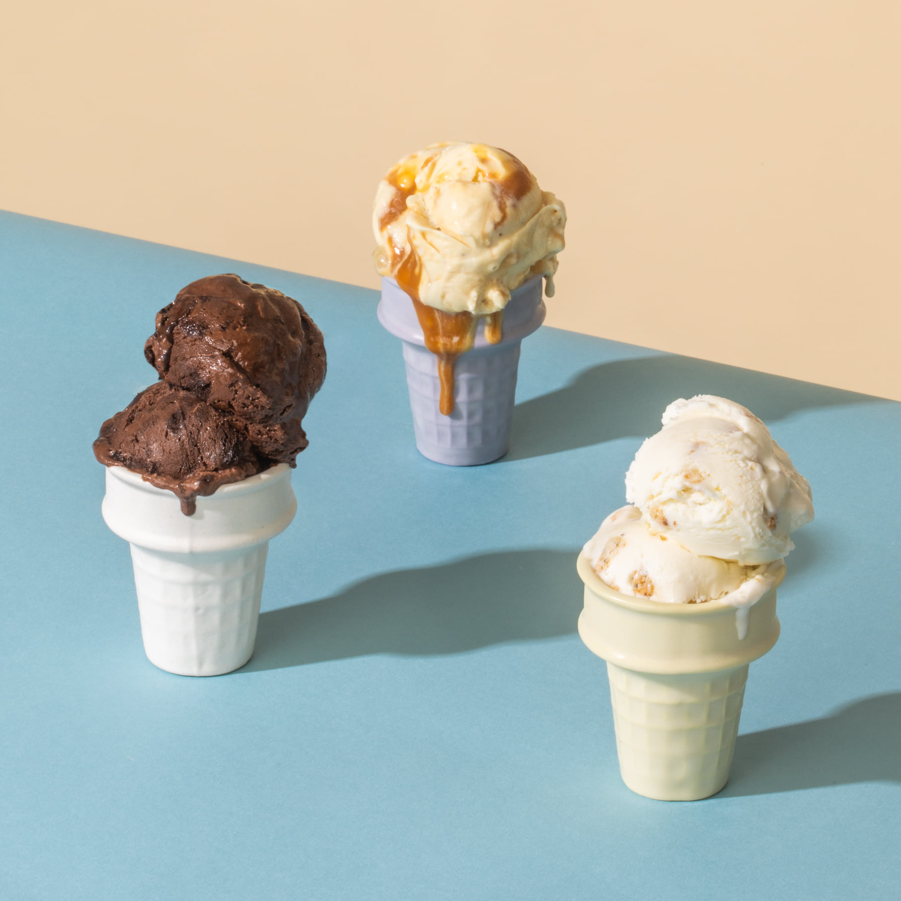 Three cake ice cream cones on a blue table (chocolate, caramel, and everything bagle ice cream)