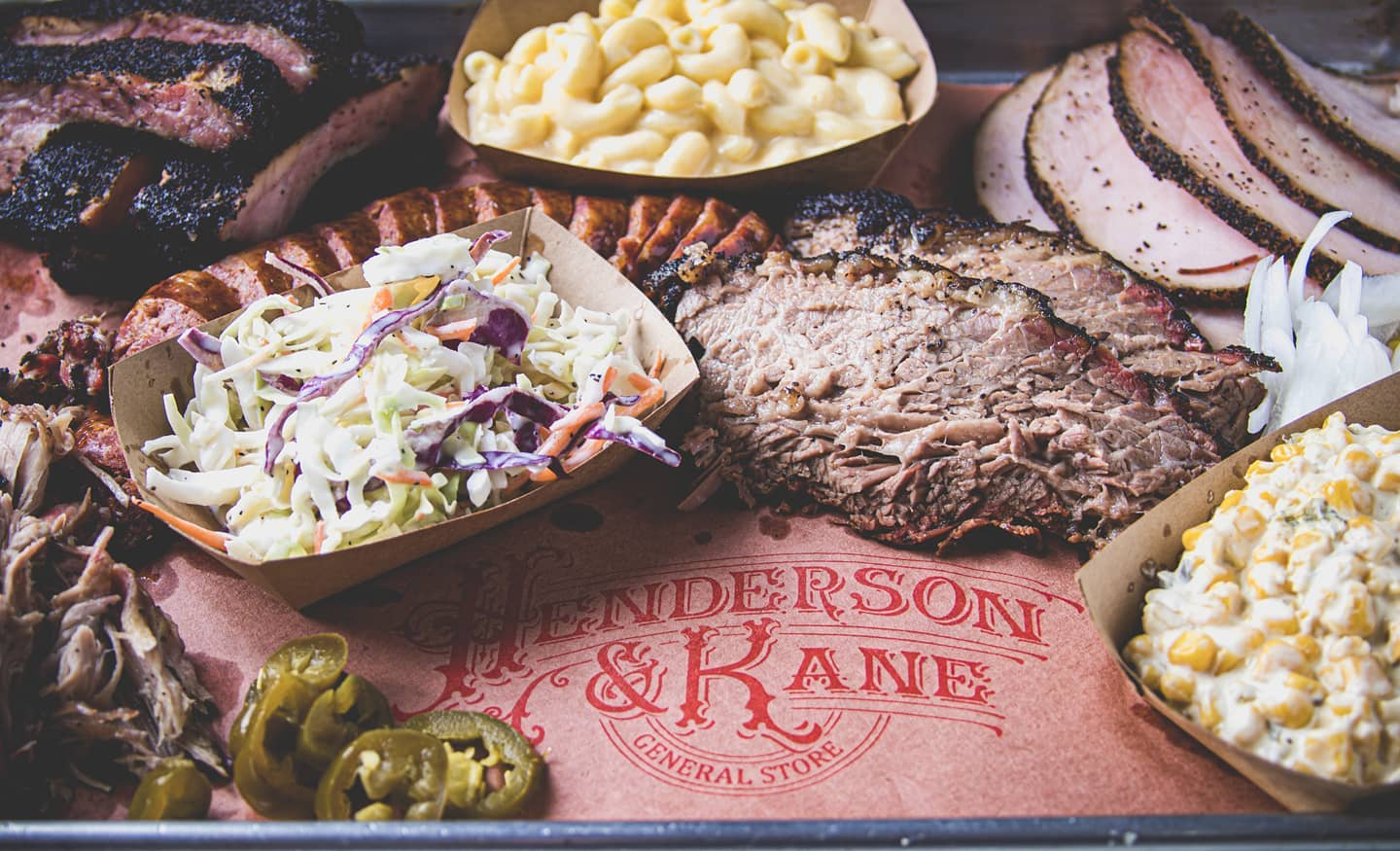 a spread of barbecue including sliced brisket, cole slaw and macaroni and cheese