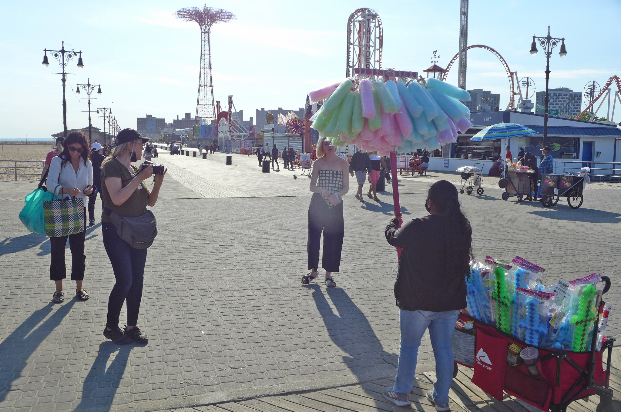 A boardwalk with a verdor holding up a pole of bags of pastel cotton candy.