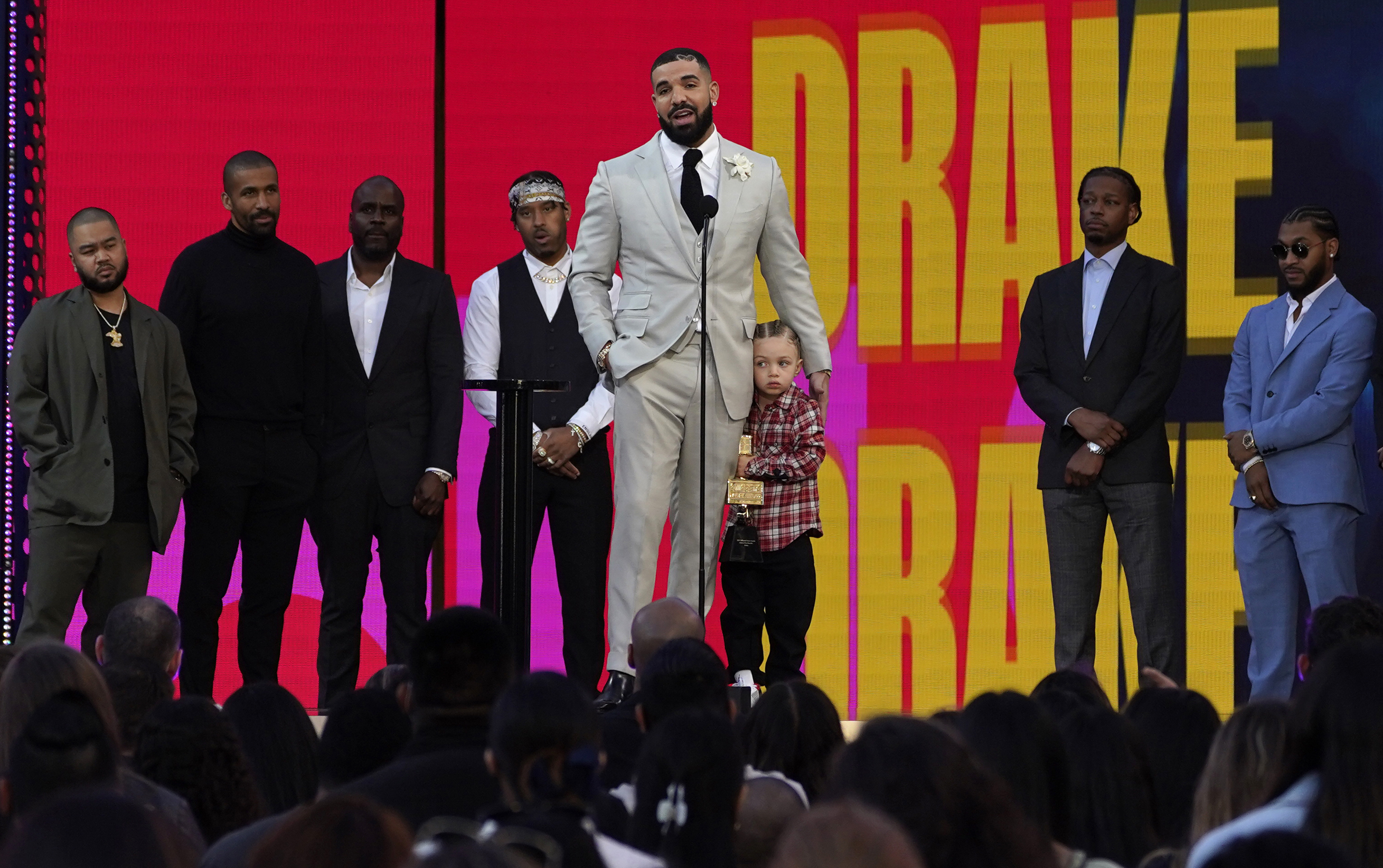 Friends and family look on as Drake accepts the artist of the decade award while he holds his son Adonis Graham at the Billboard Music Awards.