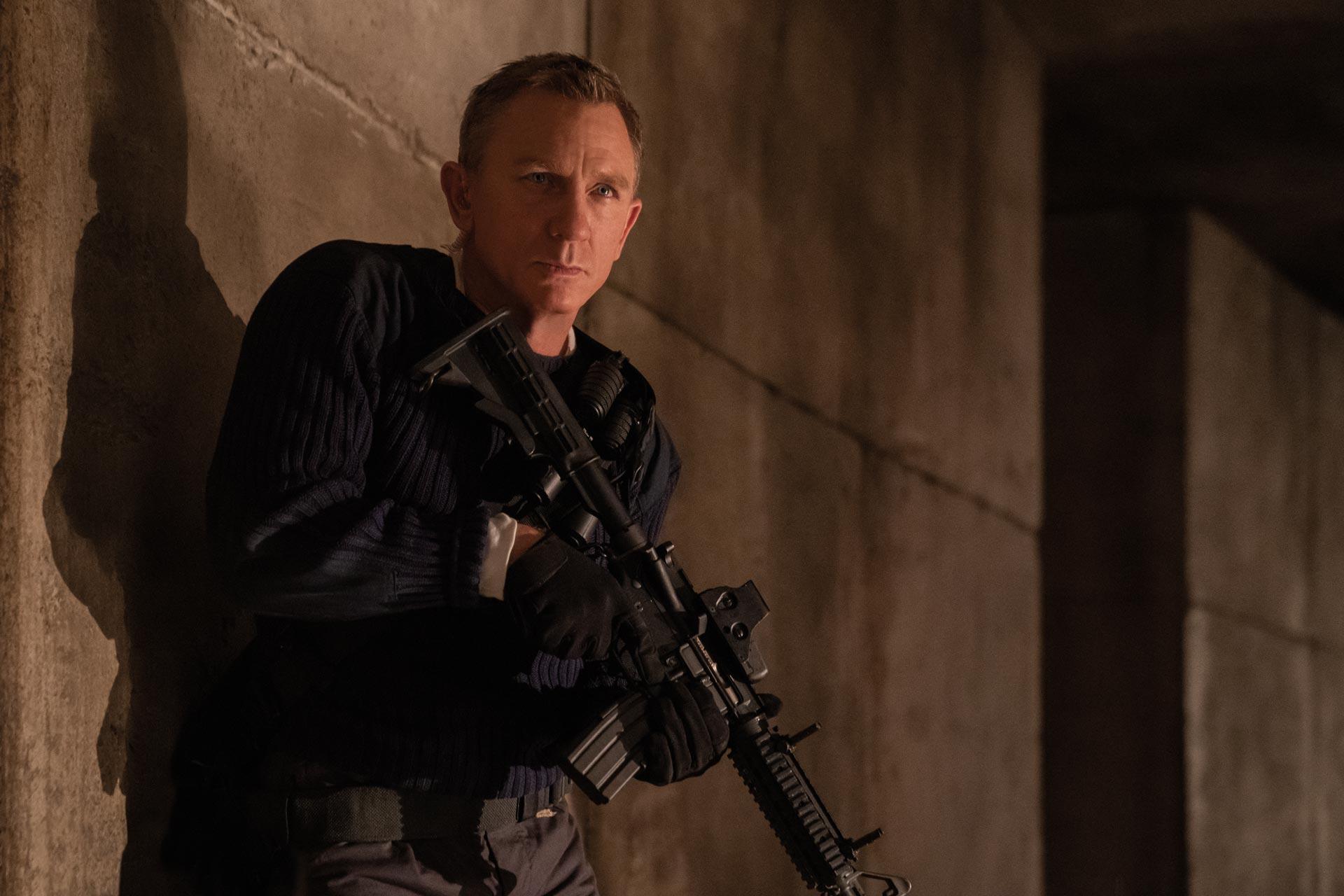 Actor Daniel Craig as James Bond, holding a large automatic weapon.