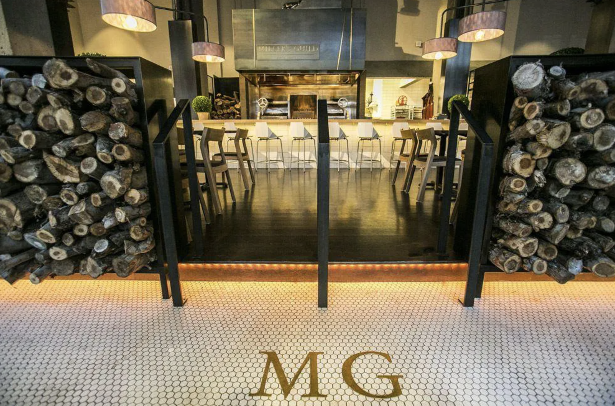 The interior of the Miller's Guild restaurant, with a gleaming steel Infierno wood-fired grill at the center surrounded by a counter and stool, and framed by two piles of chopped wood in the foreground