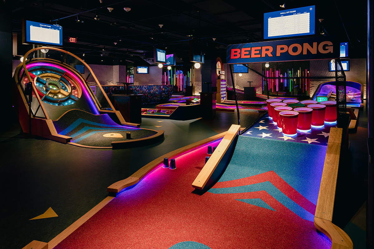 Interior view of an indoor mini golf course. The hole in the foreground is a giant beer pong setup.