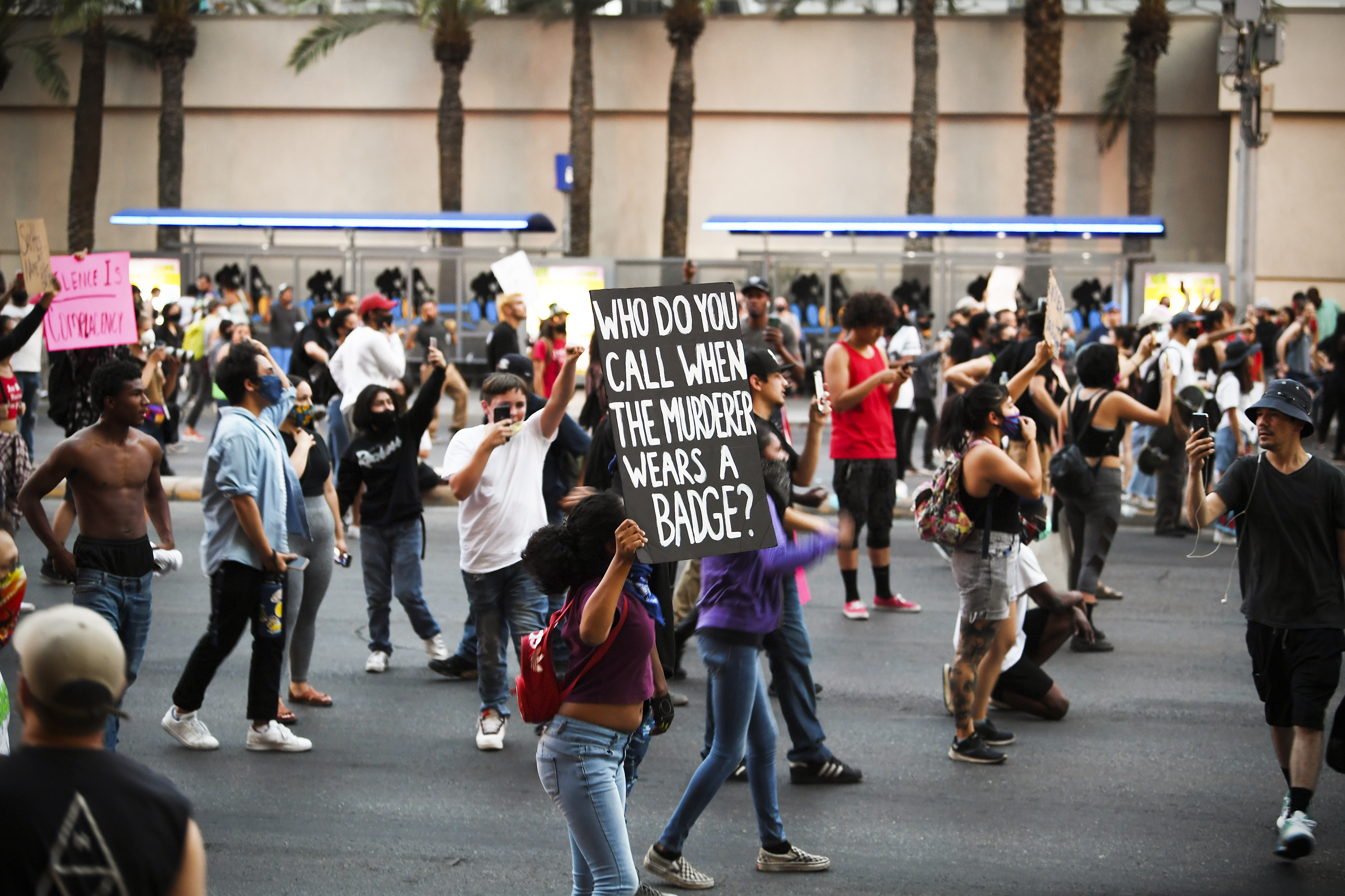 """""""Who do you call when the murderer wears a badge?"""" a black-and-white sign reads. Around the woman carrying it are socially distant knots of protesters."""