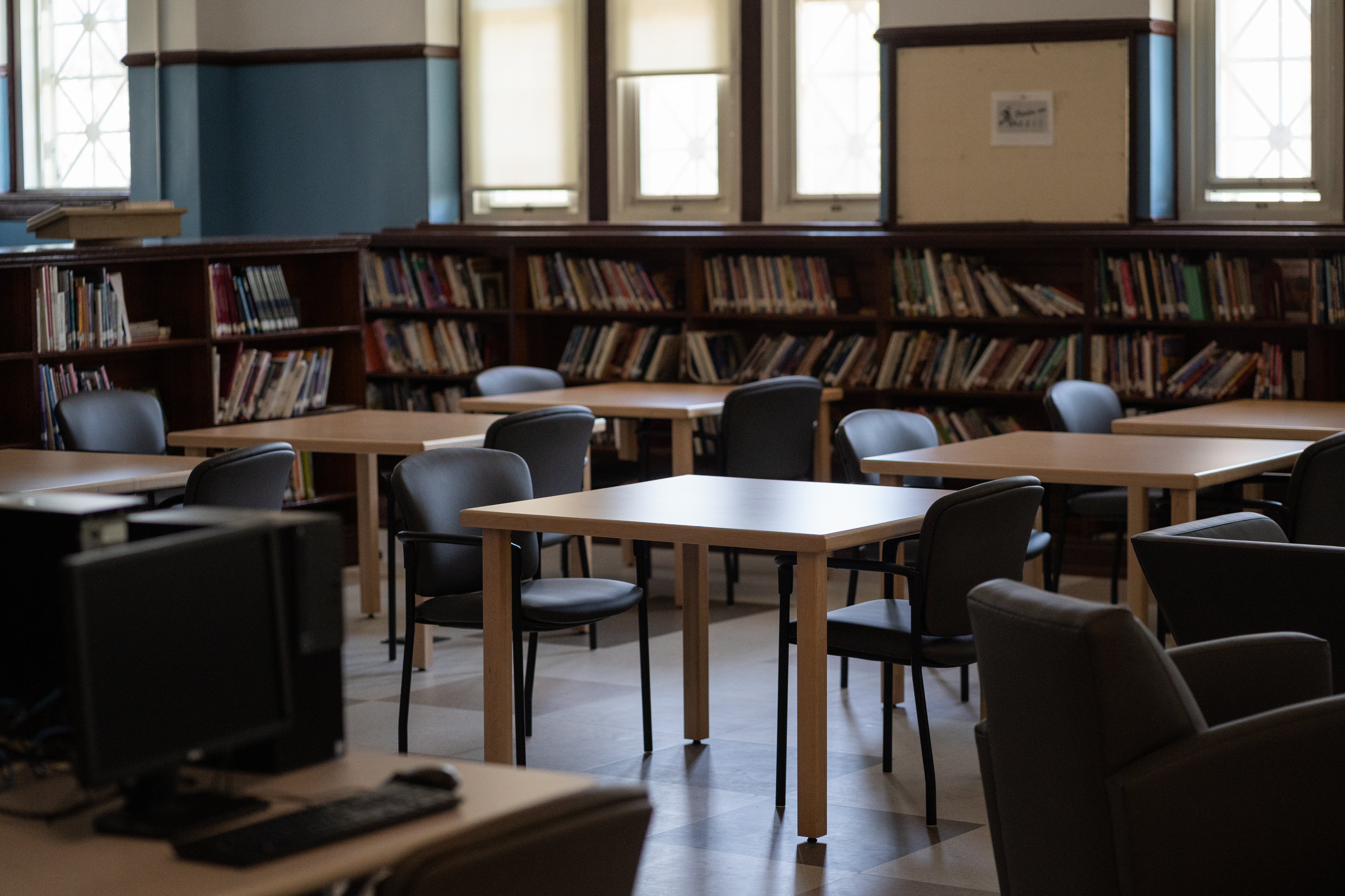 Student desks sit in an empty room at Senn High School, with bookshelves and windows in the background.
