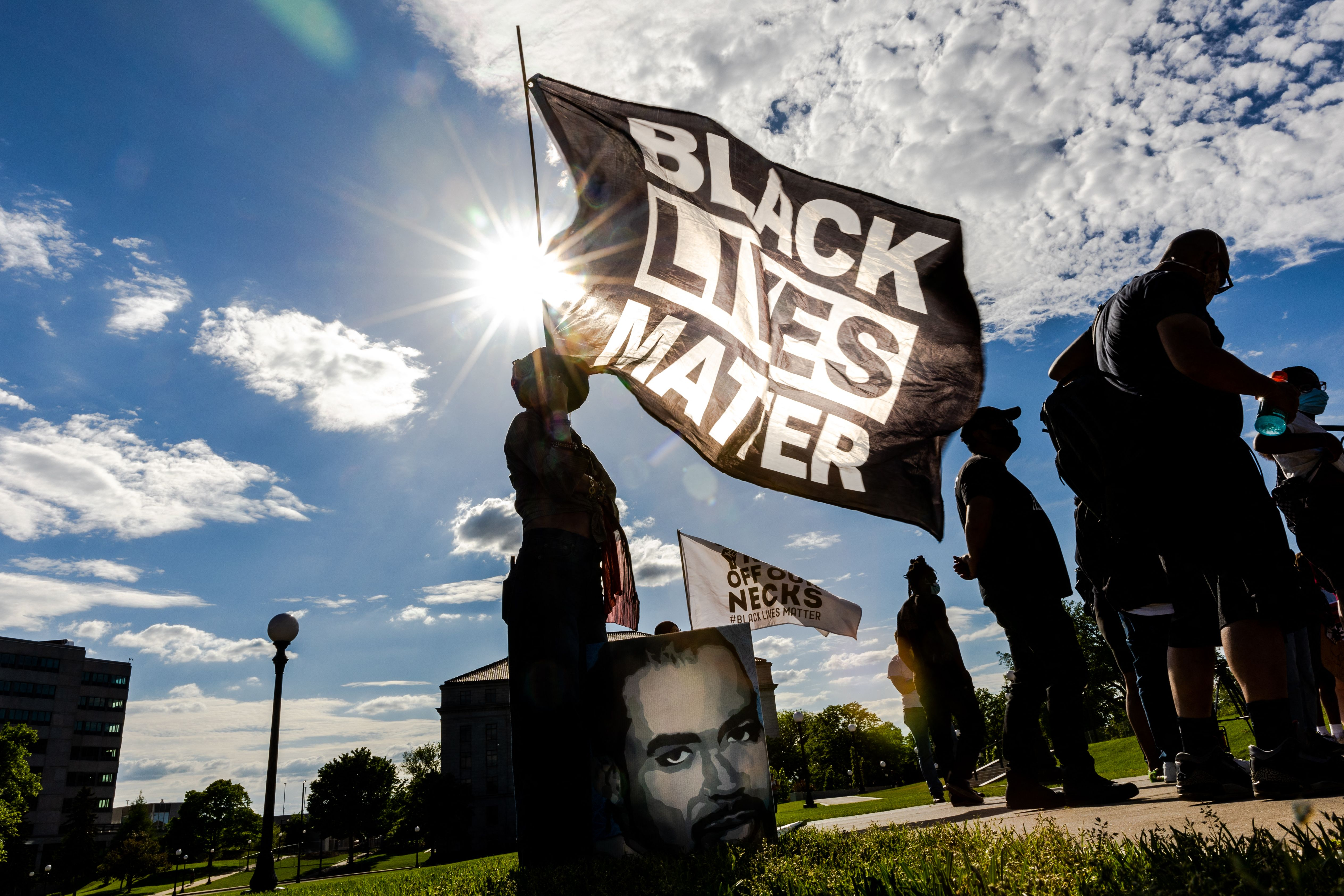 """A Black woman holds up a giant black flag, with """"Black Lives Matter"""" written on it in white. She, and the flag, are framed by the sun, which is shining brightly in a blue sky."""