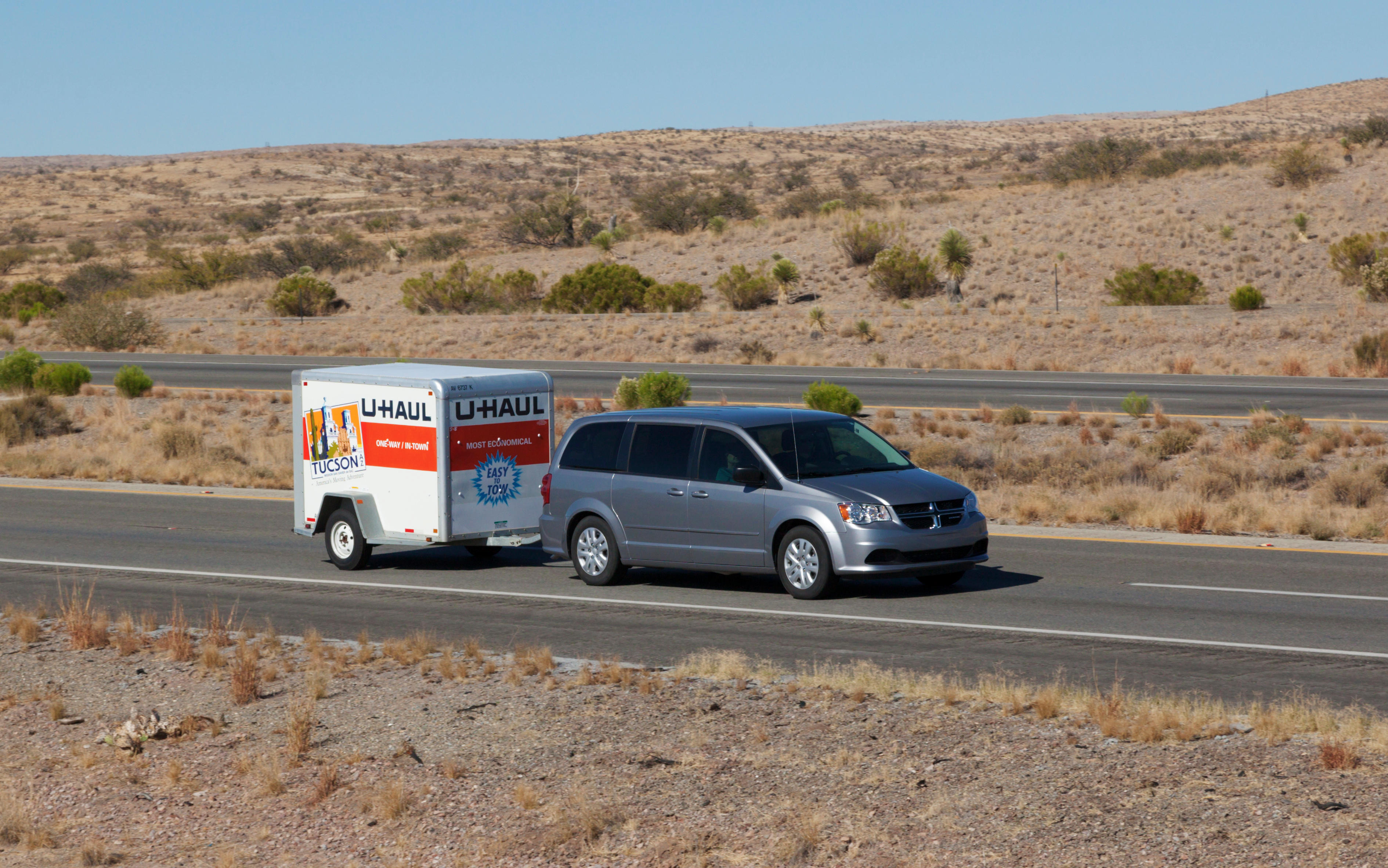 Van driving with a U-Haul trailer in the desert