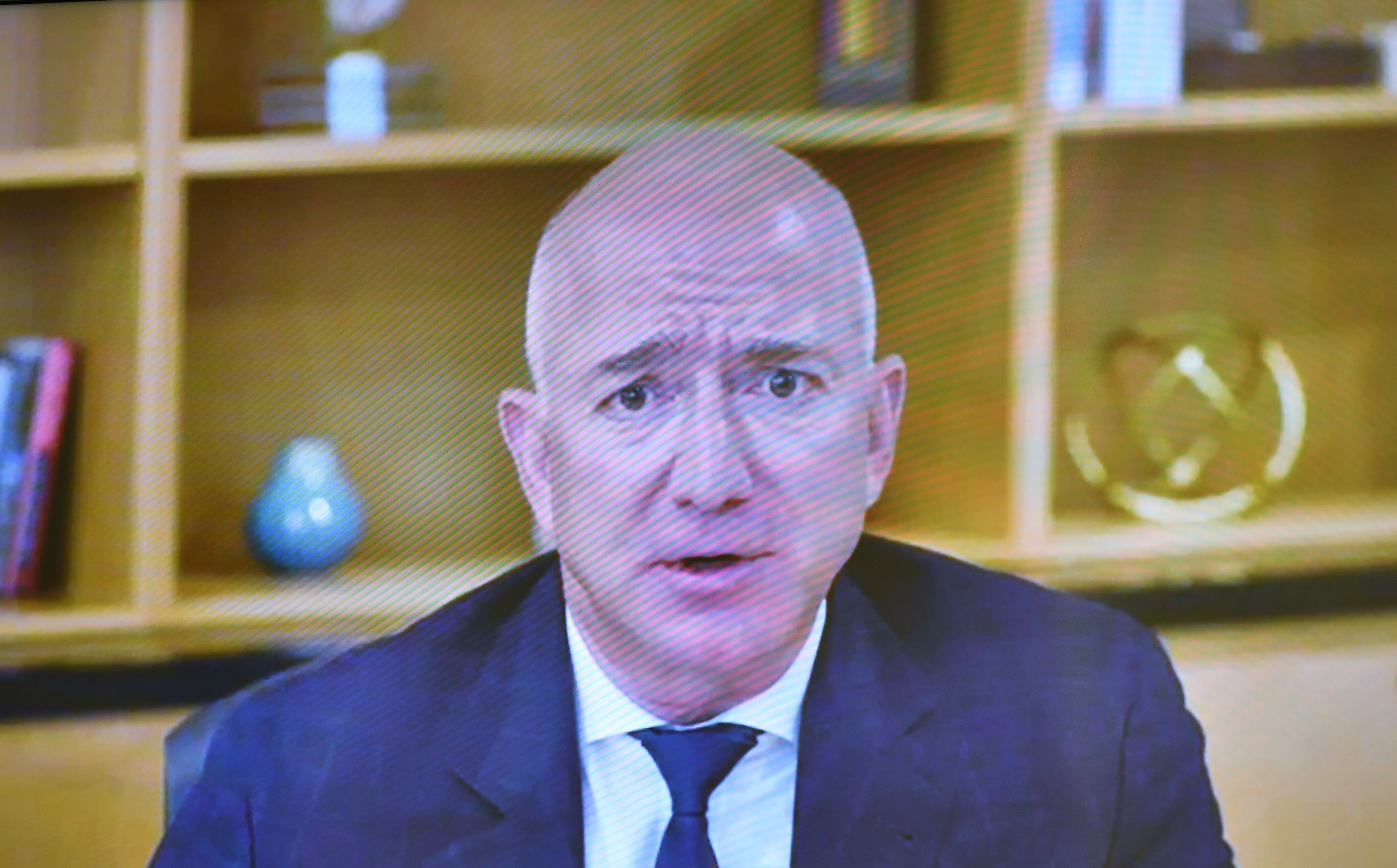 Amazon CEO Jeff Bezos appearing on a screen giving testimony to Congress.