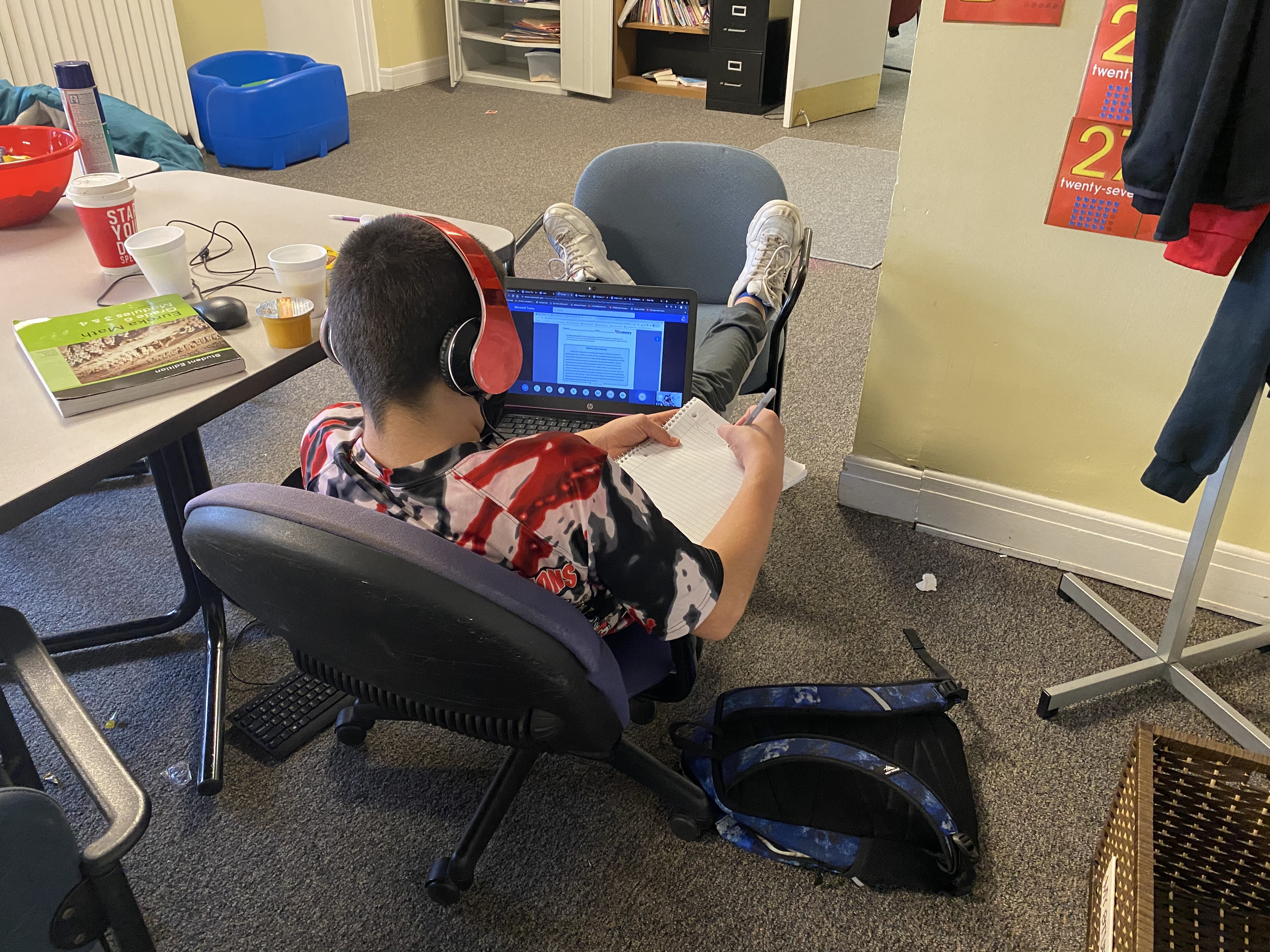 A student with headphones on sits in a chair writing in a notebook with a computer on his lap in a room.