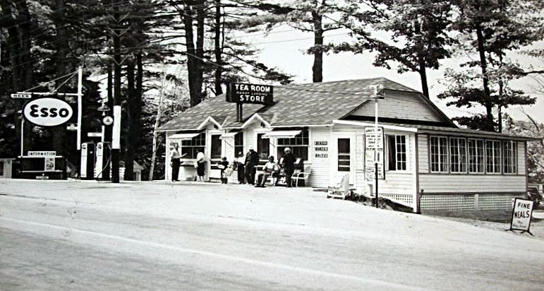 An old postcard of a gas station with a crowd hanging around out front around gas pumps