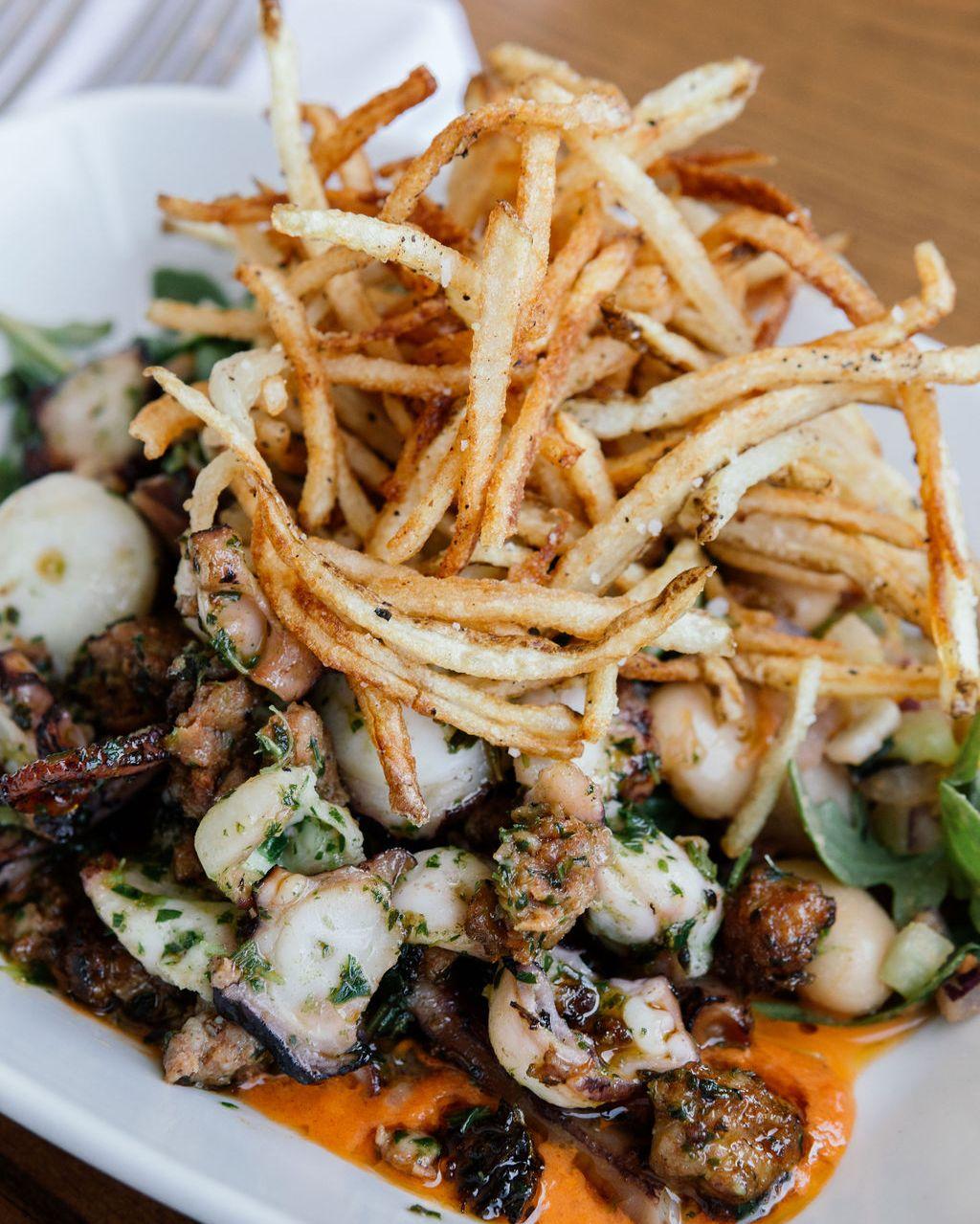 一盘上面有土豆条的海鲜