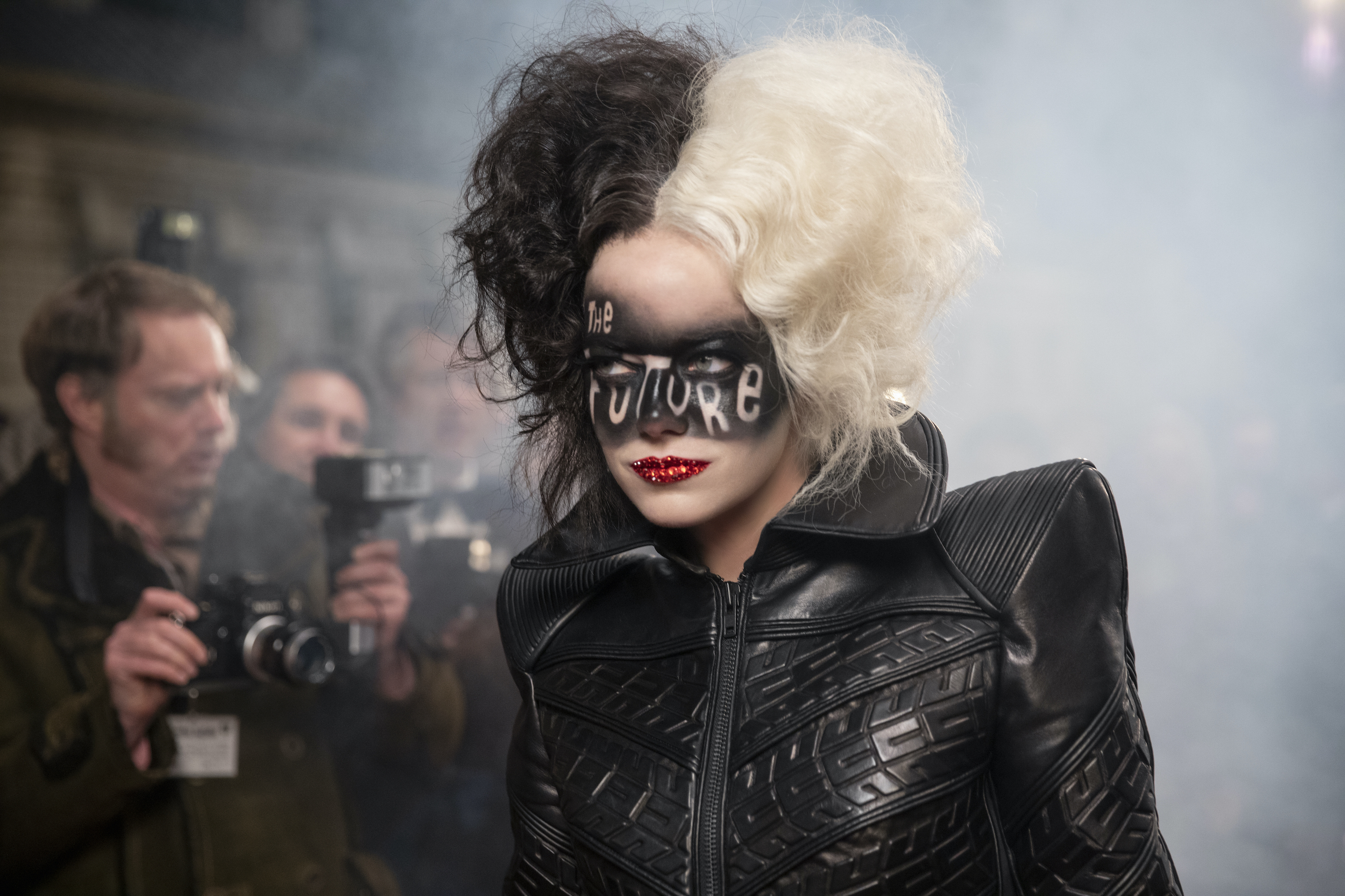 """Emma Stone as Cruella de Vil. She has black and white hair and is dressed in a structured leather ballgown. Her lips are painted with red glitter and """"the future"""" is written over her eyes in black paint."""