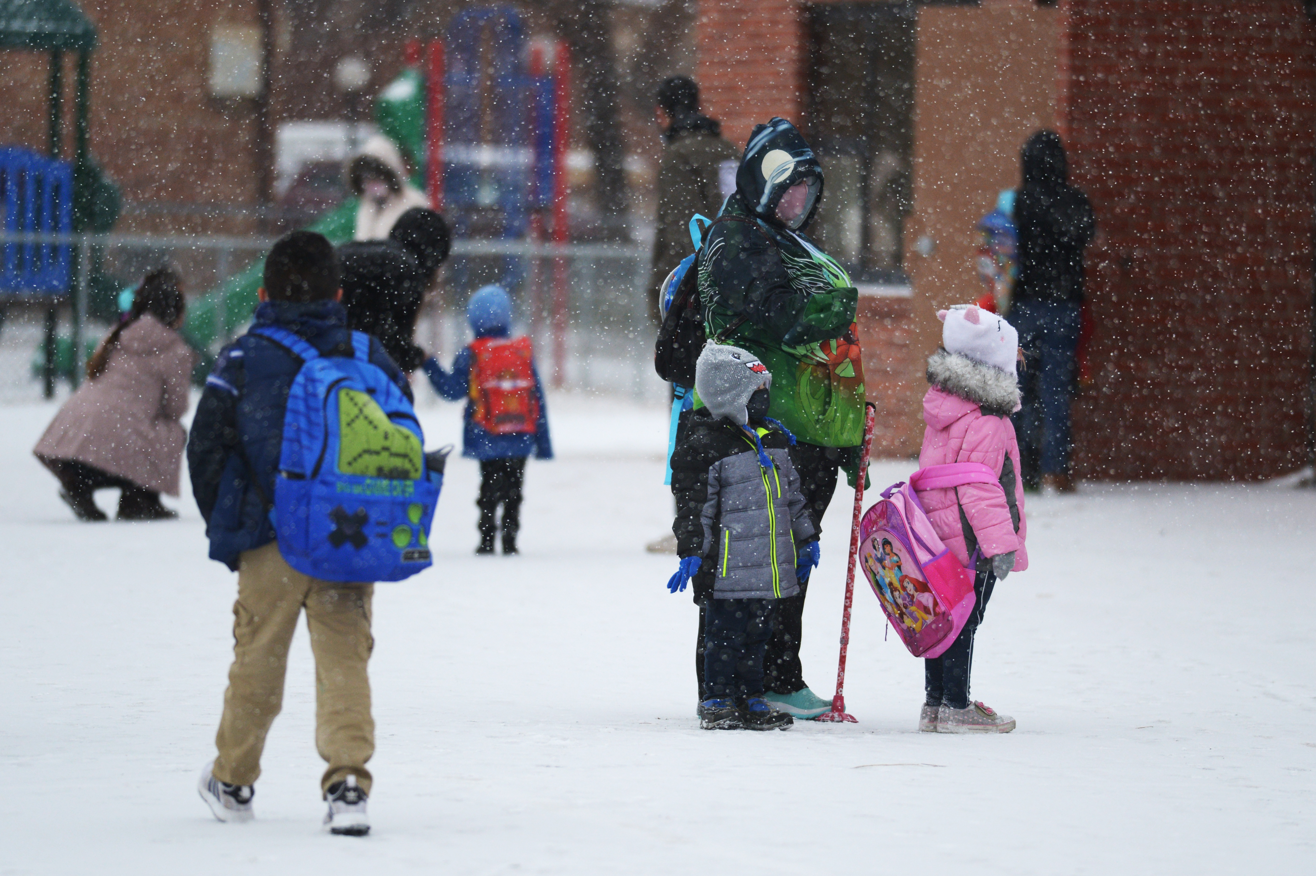 Students and parents wearing masks and winter coats wait outside a school building on a snowy day.