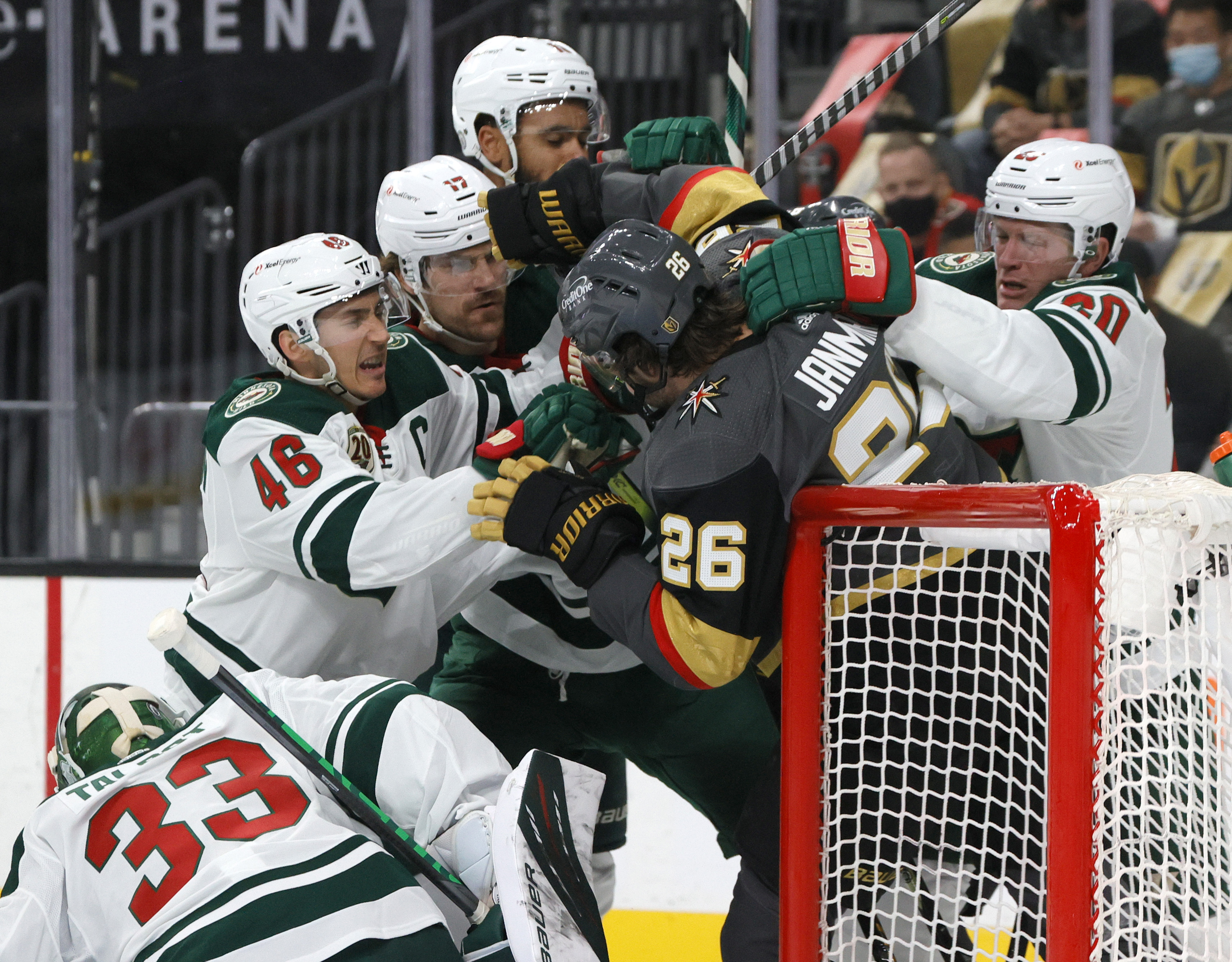 Mattias Janmark #26 of the Vegas Golden Knights is surrounded by Minnesota Wild players during a scrum at the net in the second period in Game Five of the First Round of the 2021 Stanley Cup Playoffs at T-Mobile Arena on May 24, 2021 in Las Vegas, Nevada. The Wild defeated the Golden Knights 4-2.