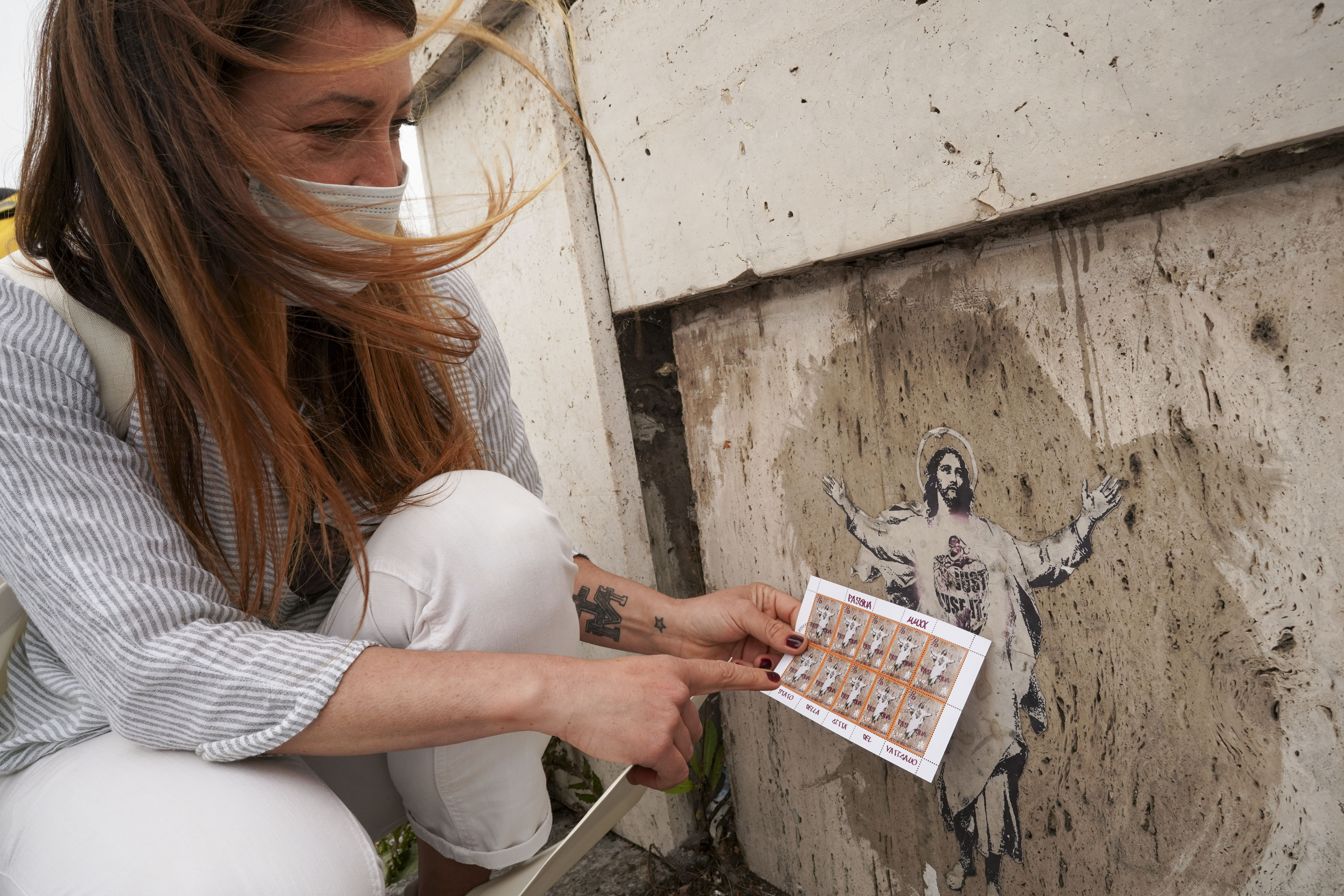 Artist Alessia Babrow holds the Vatican stamps next to her street art.