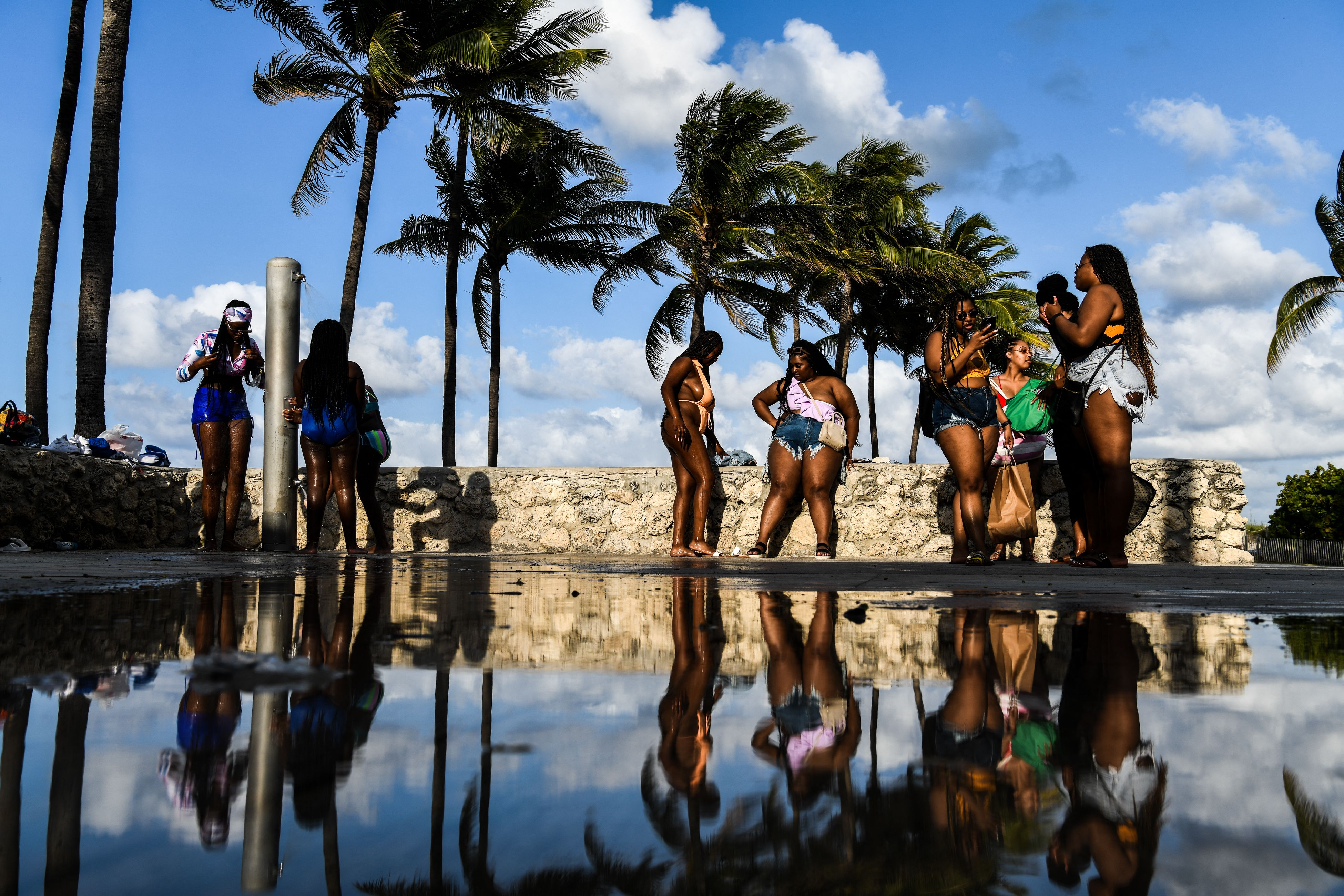 Tourists rinse their feet after getting out of the ocean in Miami Beach in May 2021.
