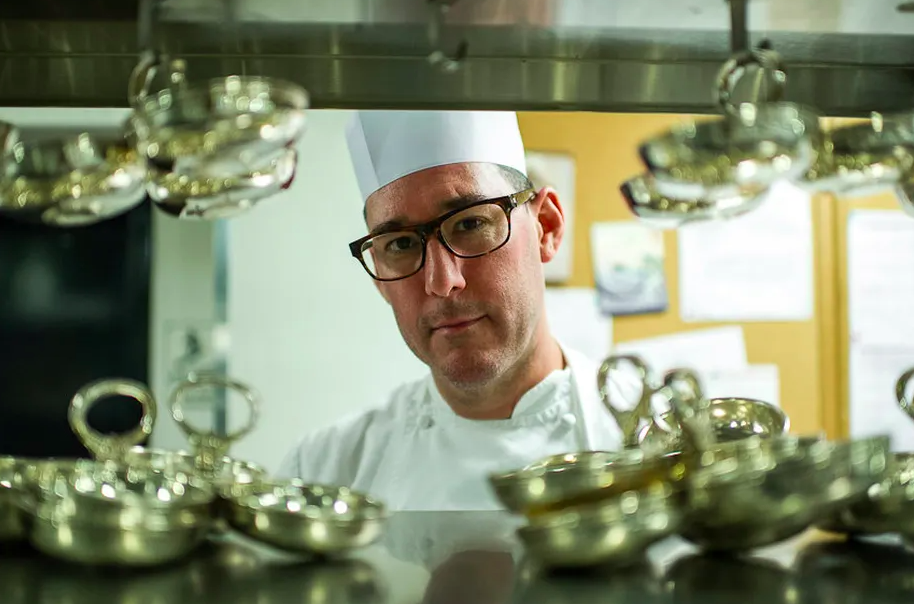 A white male chef wearing glasses with thick black rims stands behind the pass at a restaurant, wearing chef's whites.