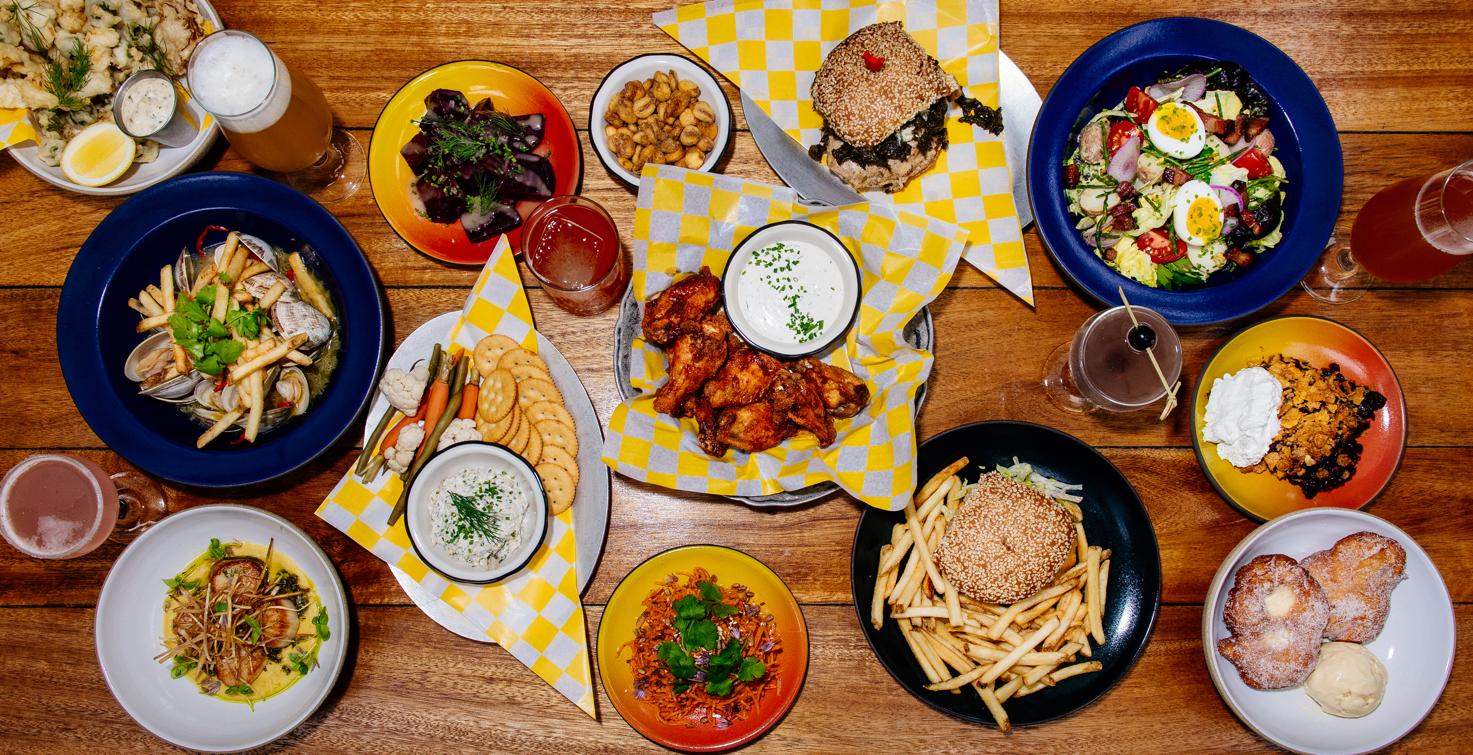 Overhead view of a wooden table full of casual plates of food, including wings, burgers, a blueberry crumble, and more