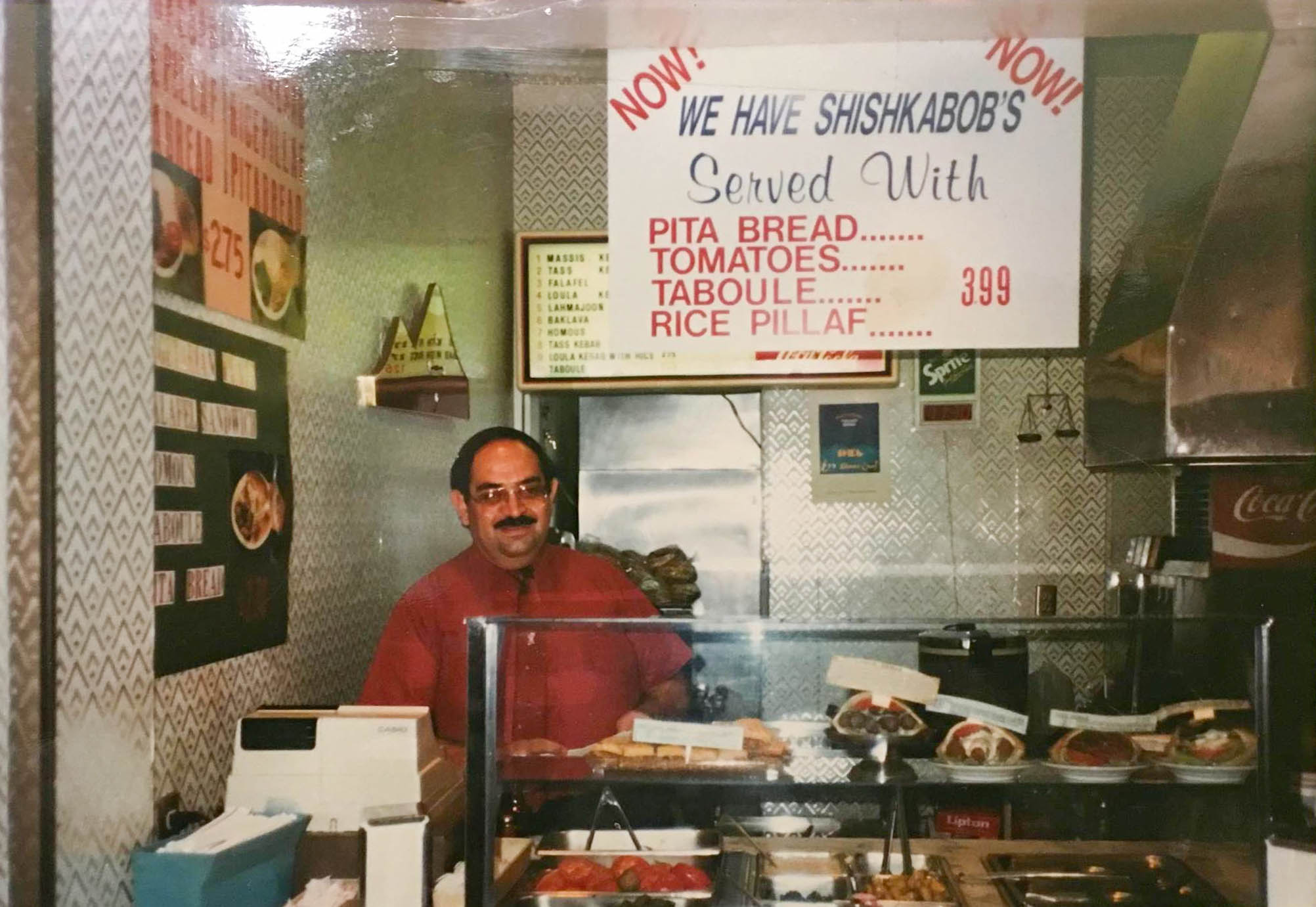 A man with a large mustache stands behind a small counter in a red shirt, serving falafel sandwiches and more.