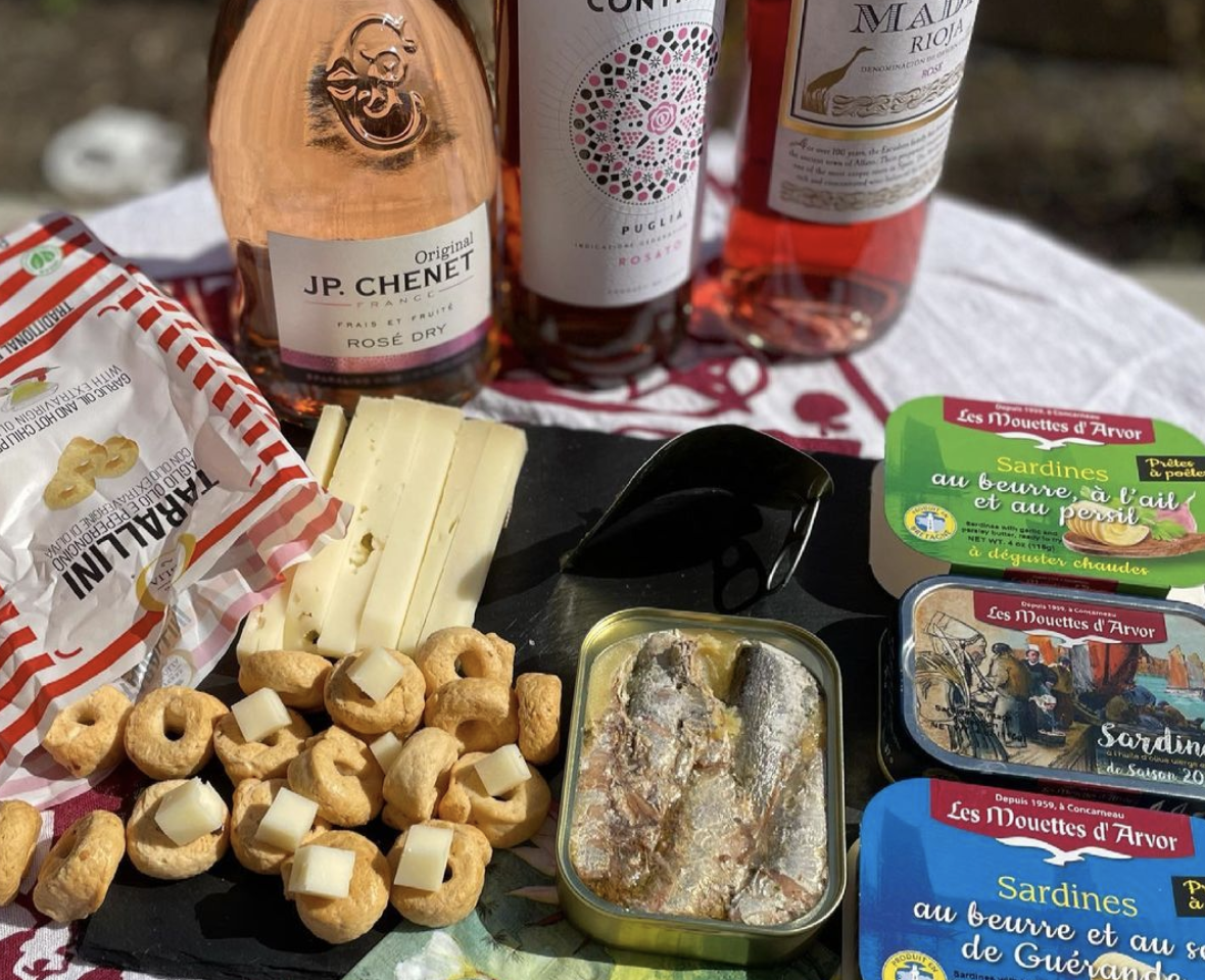Three bottles of wine, plus a variety of Italian cookies, tinned seafood, and snacks on top of a white blanket on a sunny day