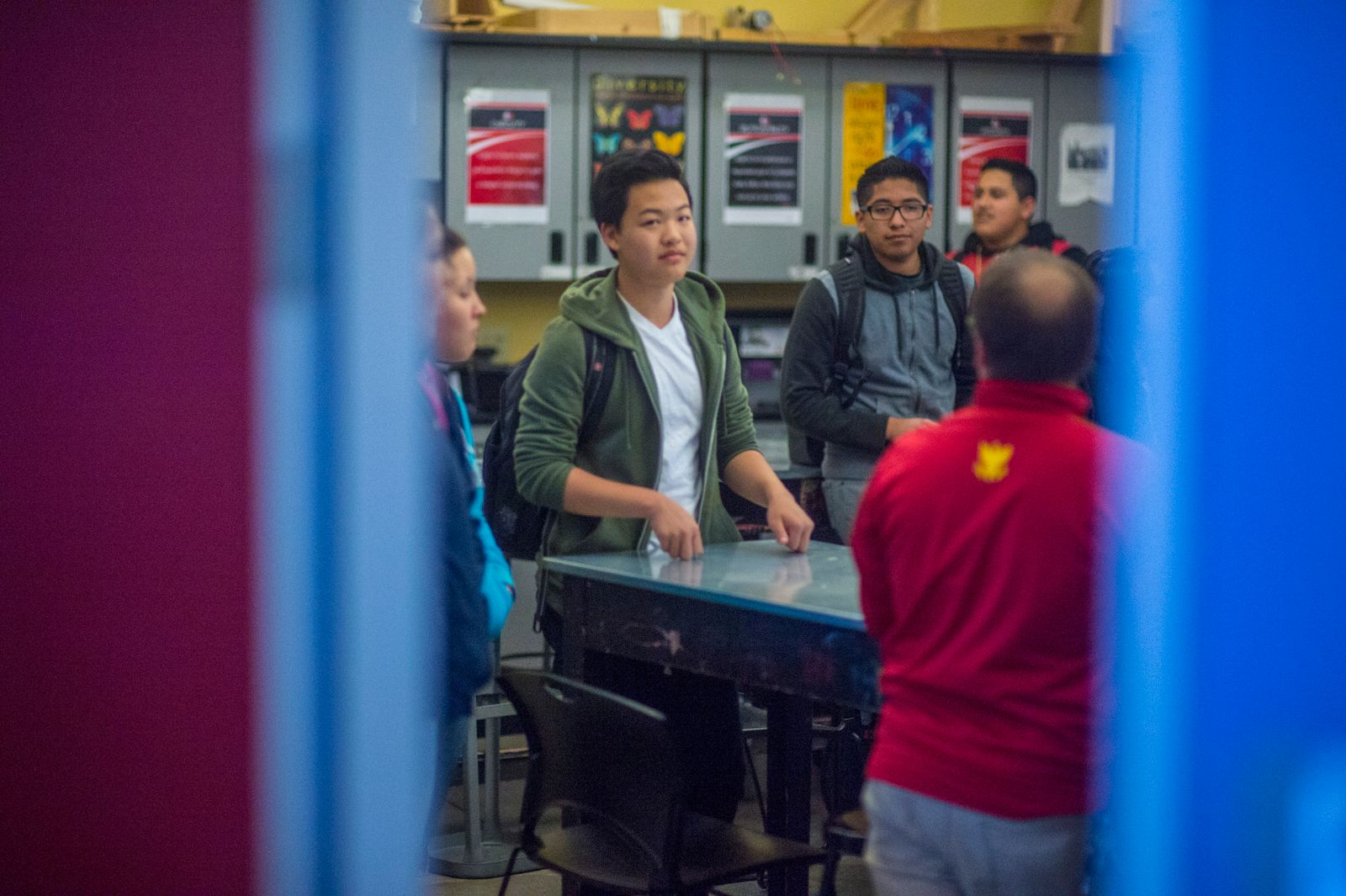 Four high school students stand around a table speaking with an older adult wearing a red jacket. They are seen through a blue doorframe.