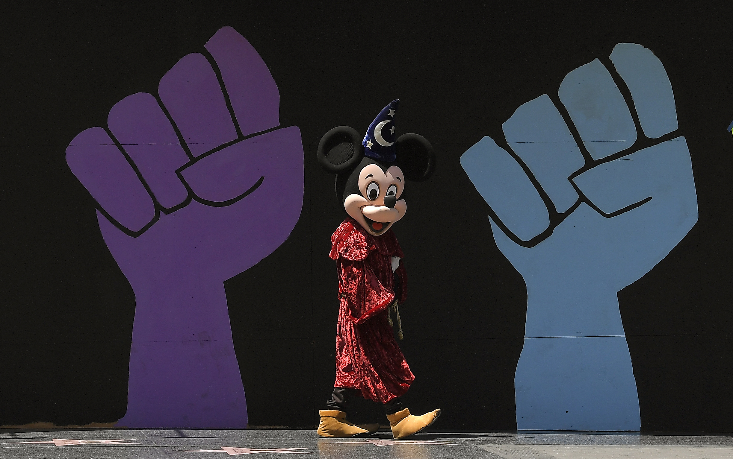 A person dressed as Mickey Mouse walks by a mural in Los Angeles.