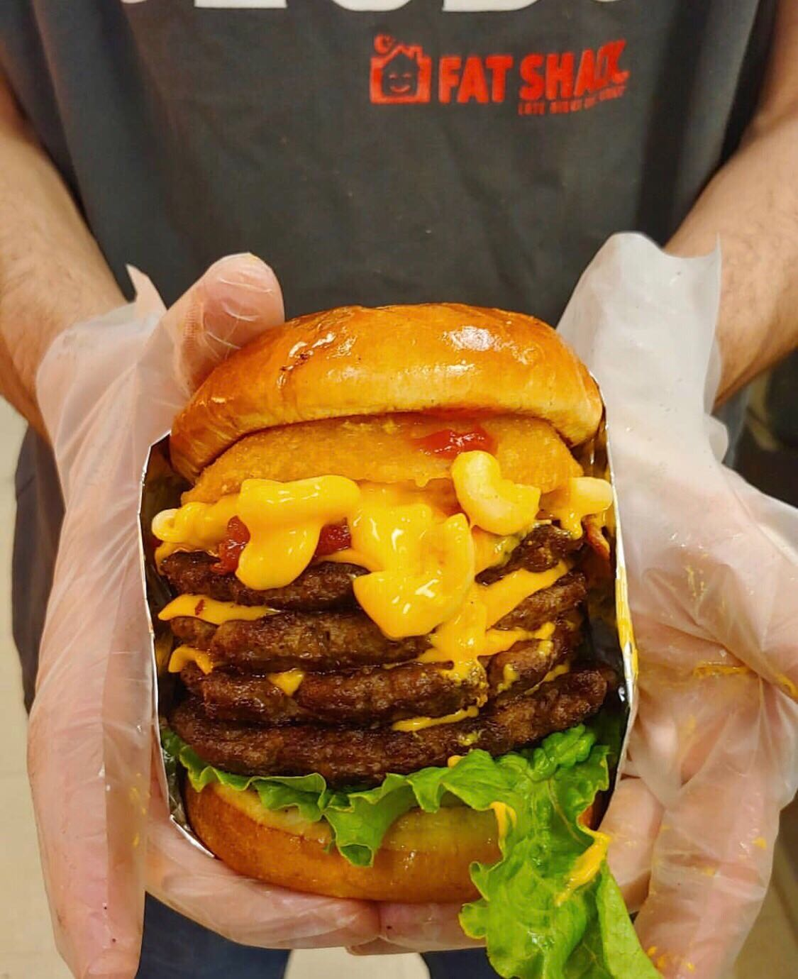 A burger with four patties dripping with cheese