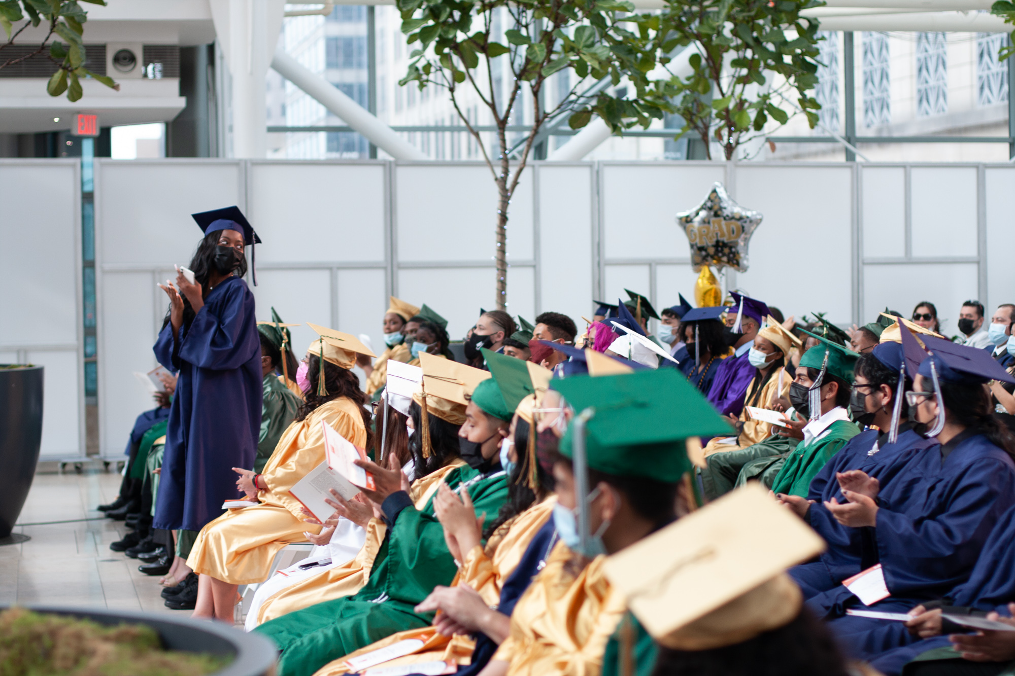 A girl in a blue cap and gown stands in a row of students wearing blue, gold and green graduation gowns and claps.