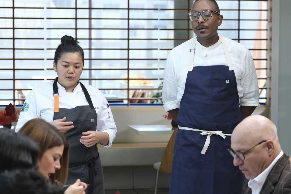Two chefs stand in front of a table with diners