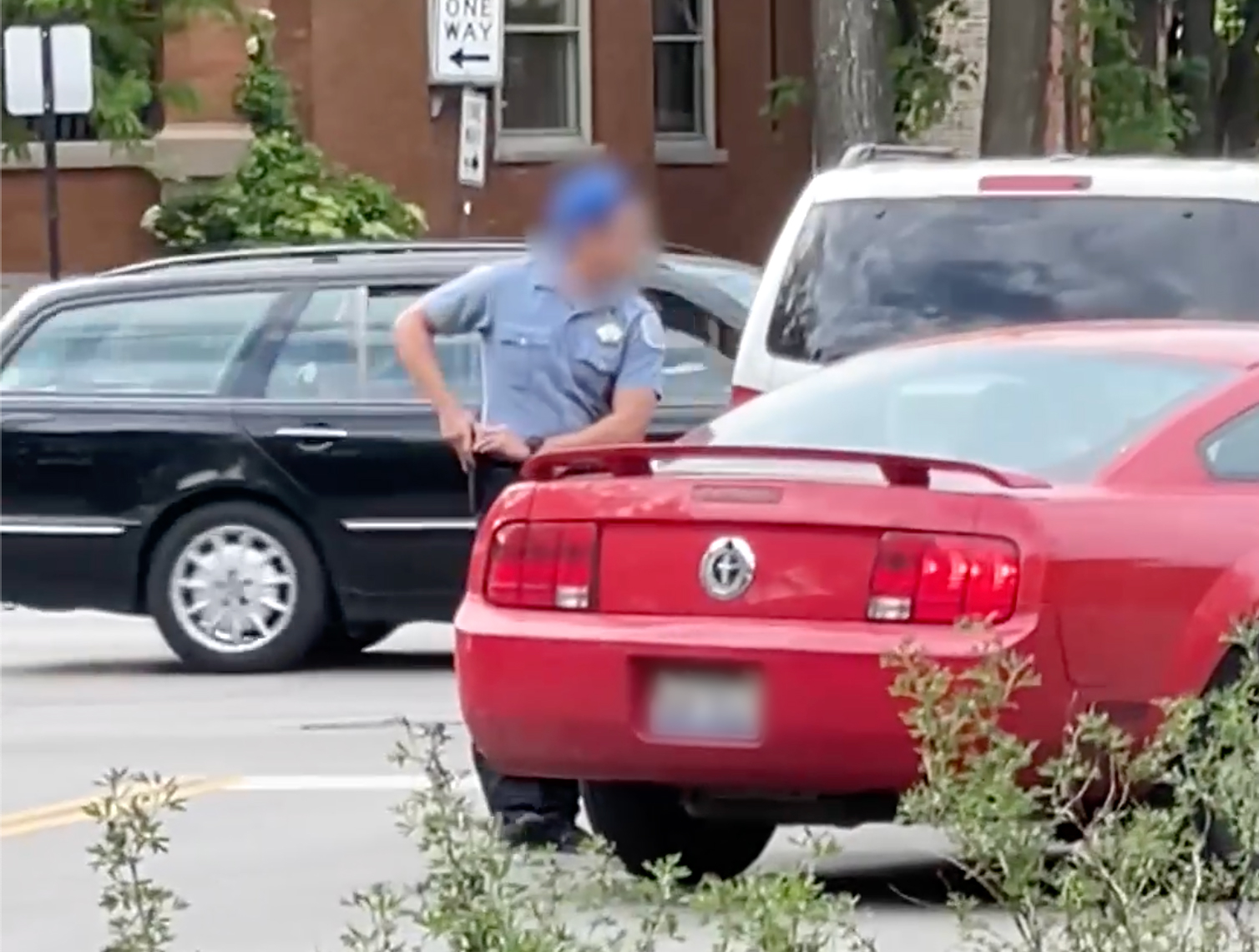 A Chicago police officer holsters his weapon after being involved in an apparent road rage incident in Logan Square.