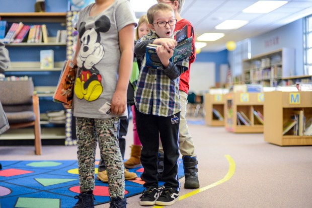 Vivian Elementary School third-grader Ayden Bobbitt, 9, reacts as he reads his book in the library checkout line Friday, Dec. 6, 2019, in Lakewood. Jeffco Public Schools.