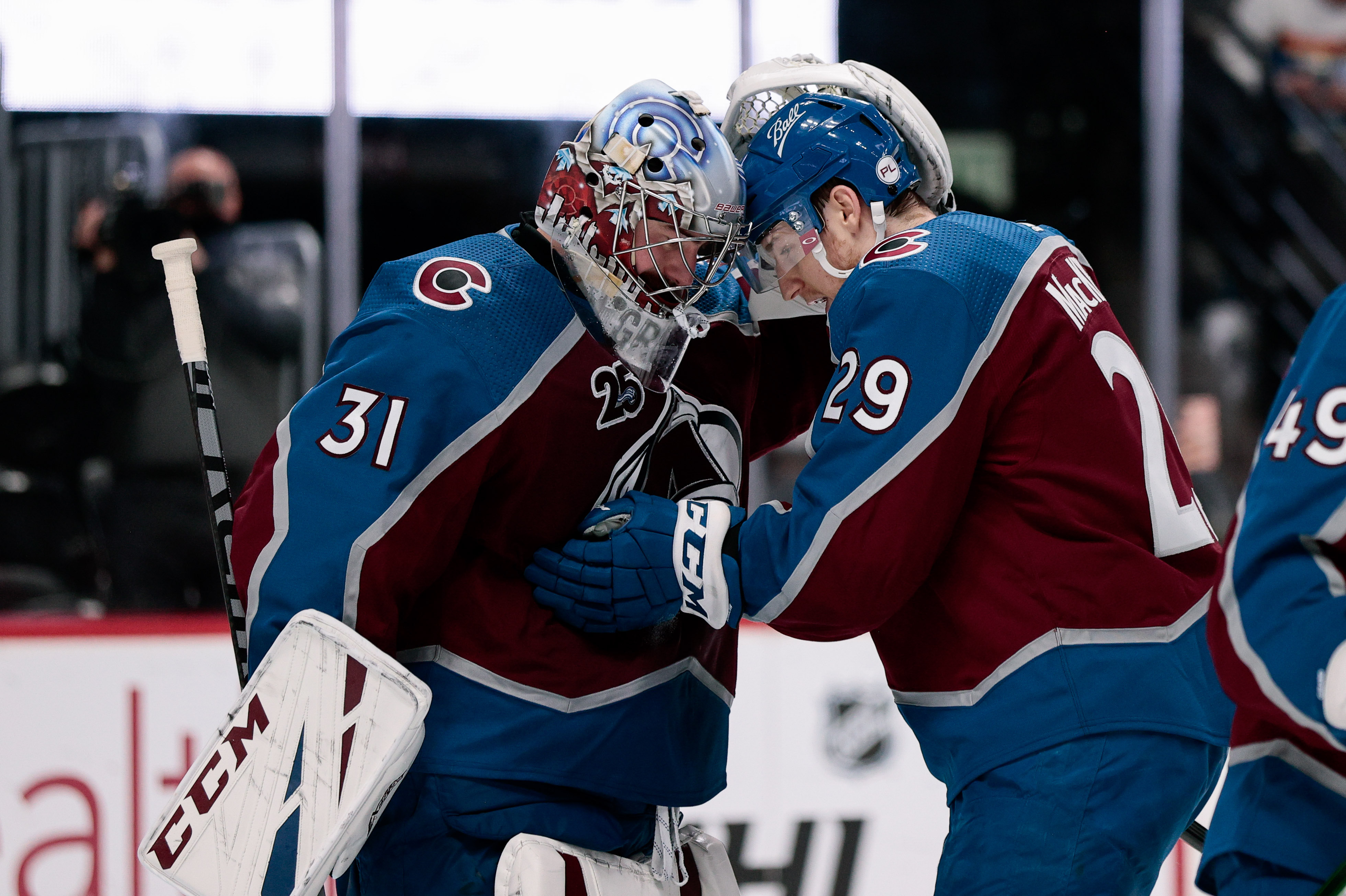 Colorado Avalanche goaltender Philipp Grubauer celebrates with center Nathan MacKinnon after winning game two of the first round of the 2021 Stanley Cup Playoffs against the St. Louis Blues at Ball Arena.