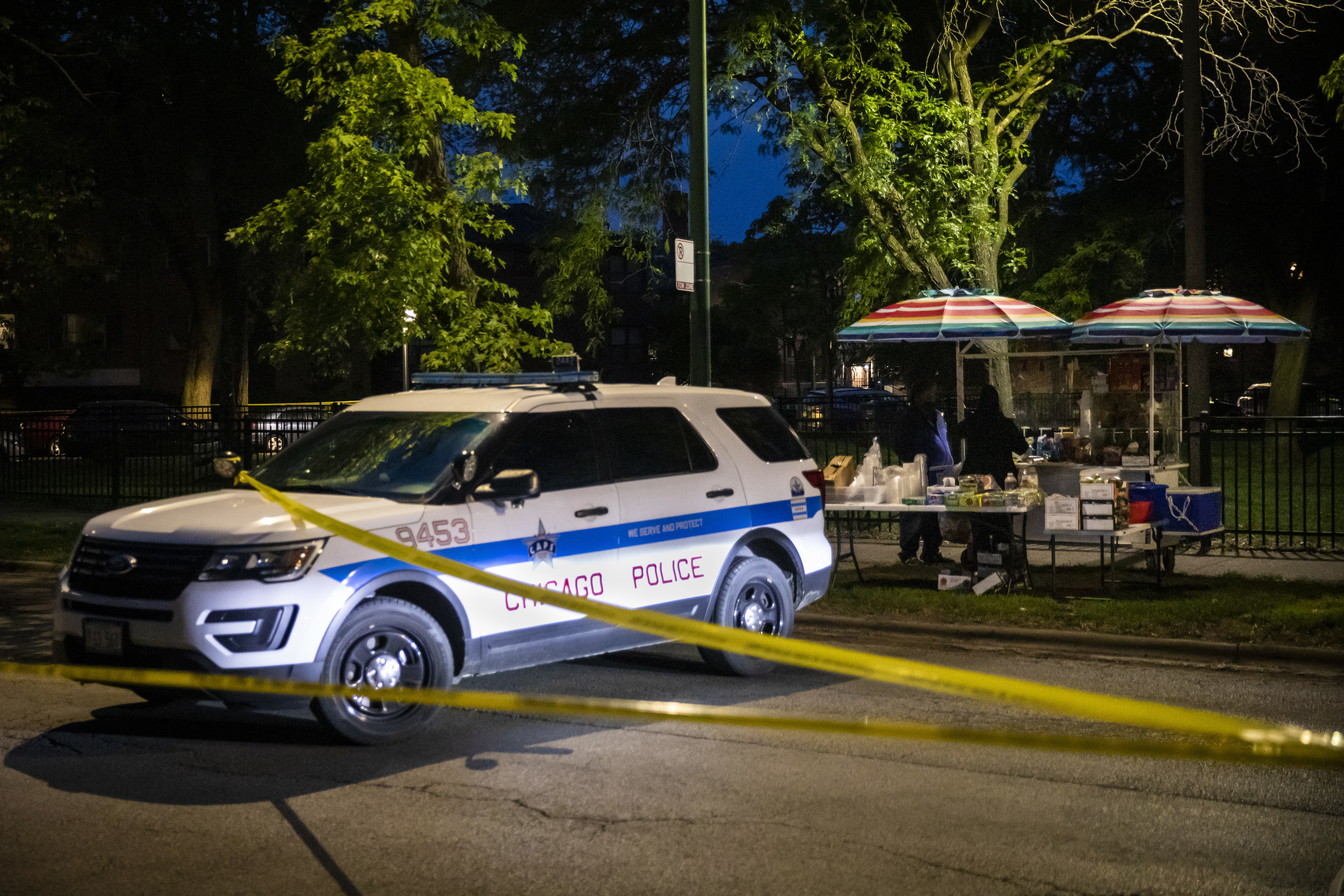Chicago police investigate in the 7300 block of North Rogers Avenue, near an elotera stand outside Pottawattomie Park in Rogers Park, where police said a 28-year-old man was shot multiple times Sunday night.