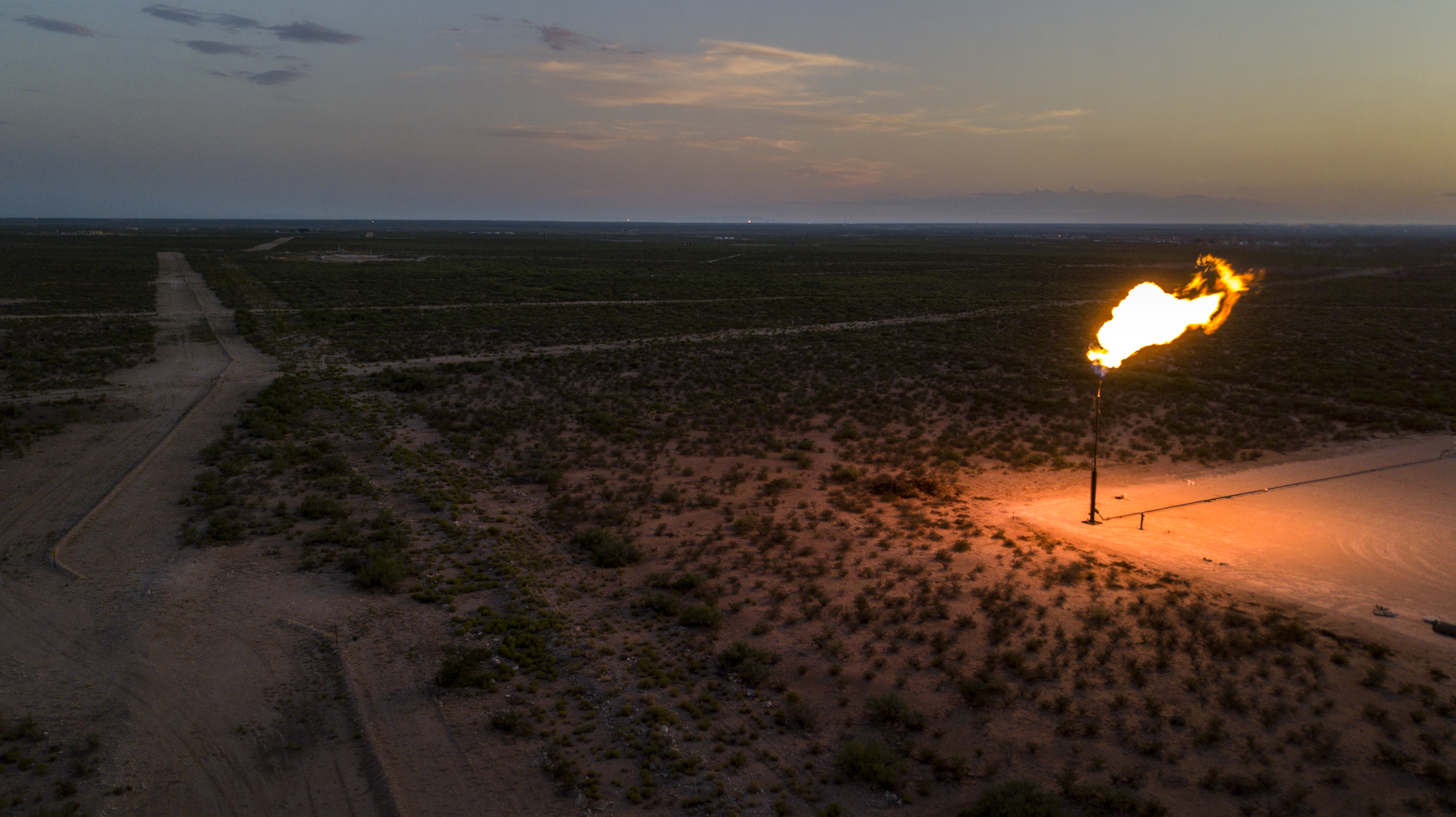 A vertical pipe in the middle of nowhere with a gas flare burning from its top.