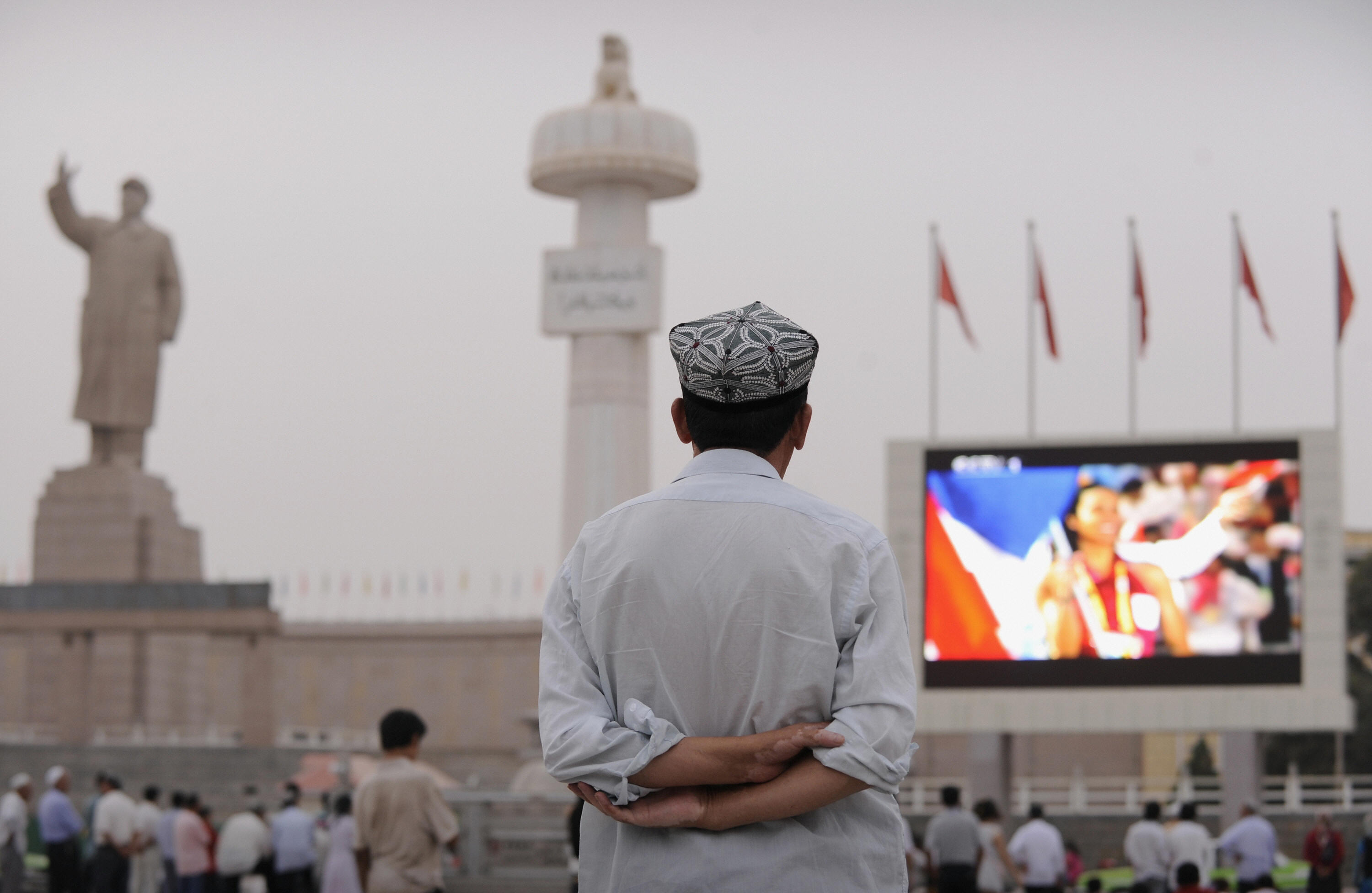 A Uyghur man watches the opening ceremony of the Olympic Games on a big screen in Kashgar in Xinjiang province on August 8, 2008.