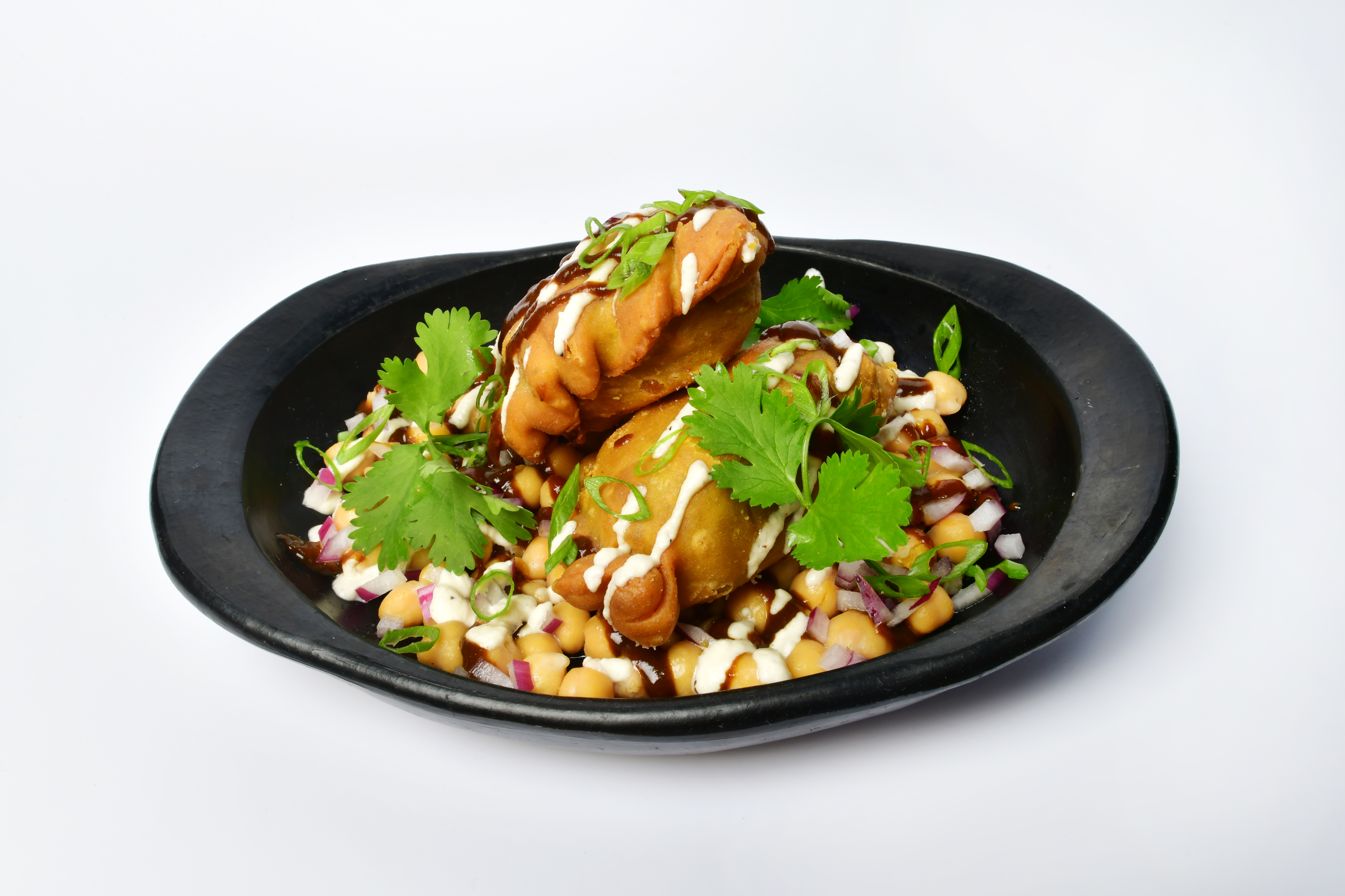 Samosa chat sits in a round black bowl.